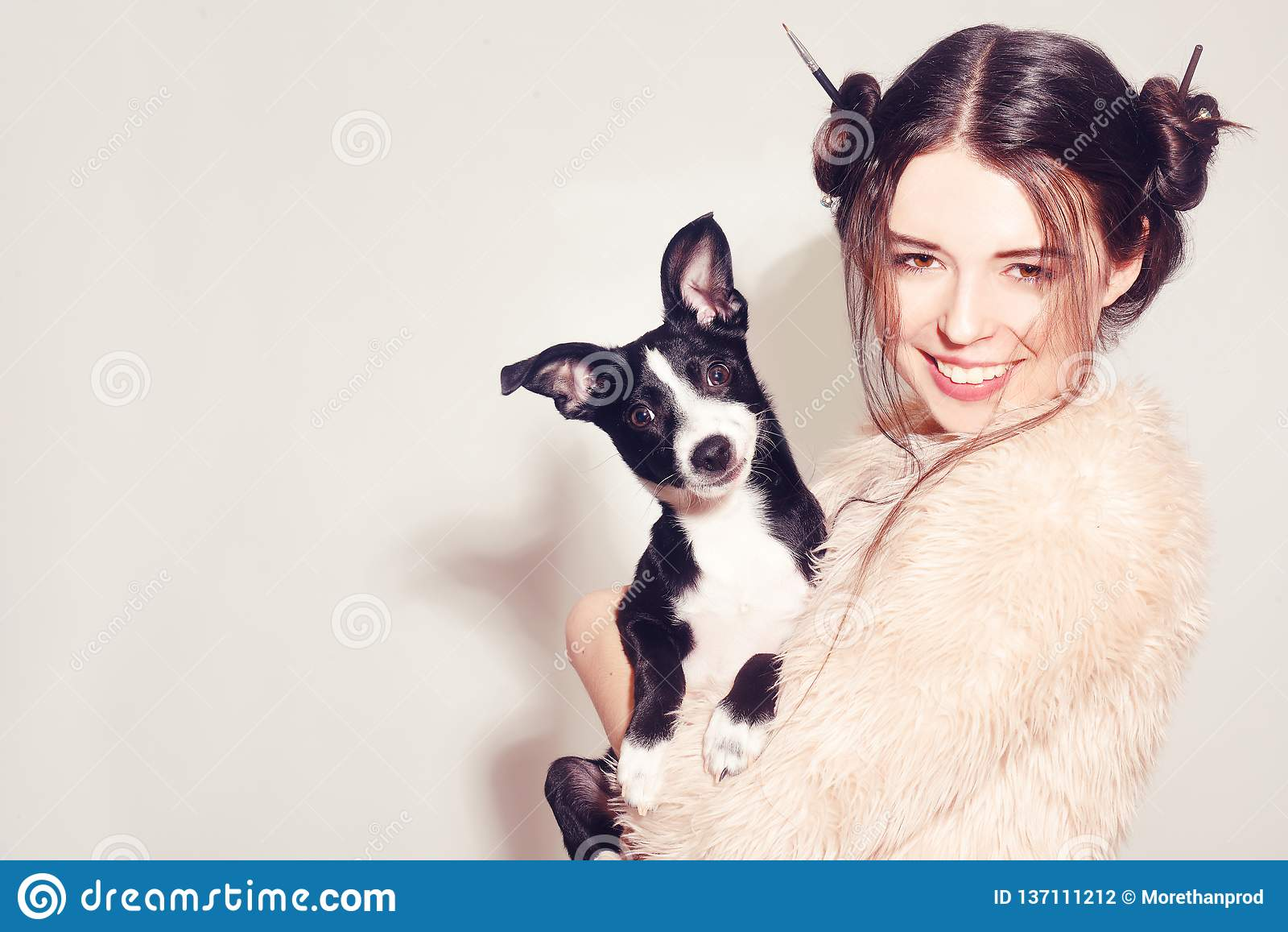有小狗的愉快的女孩 妇女获得与她的狗的乐趣 获得狗的所有者与宠物的乐趣 在人和狗之间的友谊 宠物