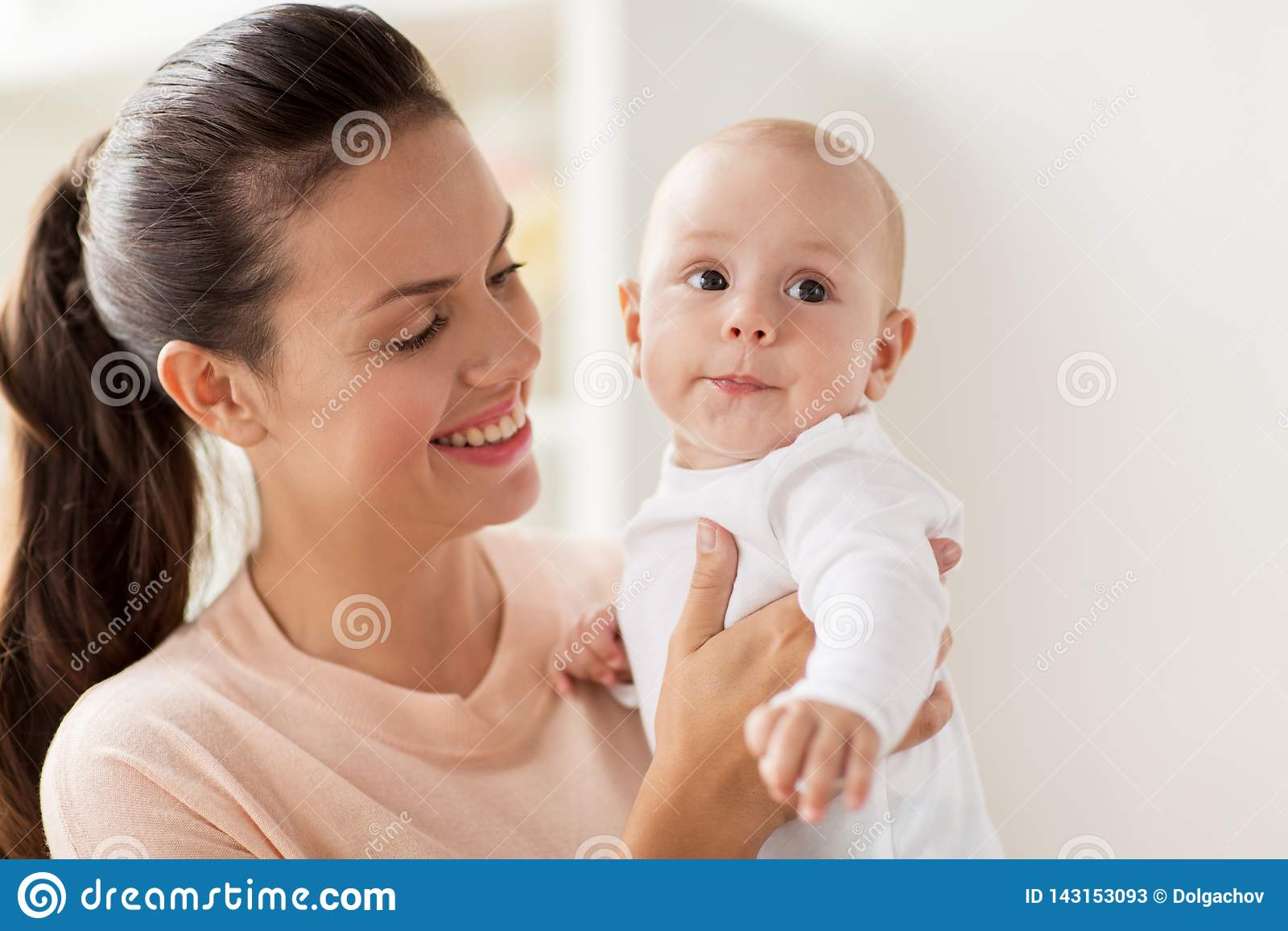 有小男婴的愉快的母亲在家