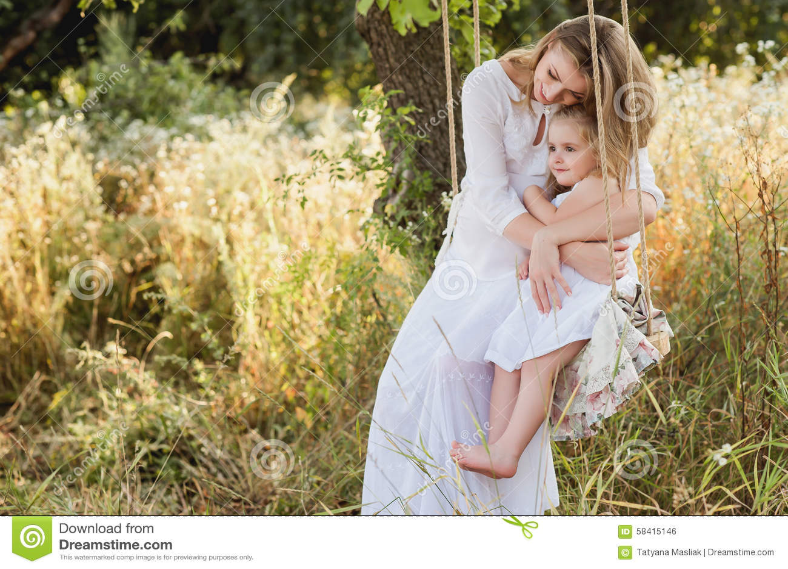 有小白肤金发的女孩的怀孕的美丽的母亲一件白色礼服的坐摇摆,笑,童年,放松