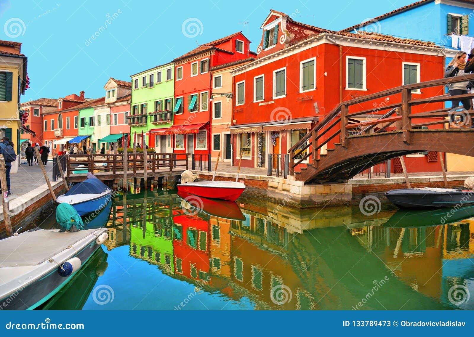 有小色的房子、游人木桥的和美好的水反射的Burano海岛美丽如画的街道