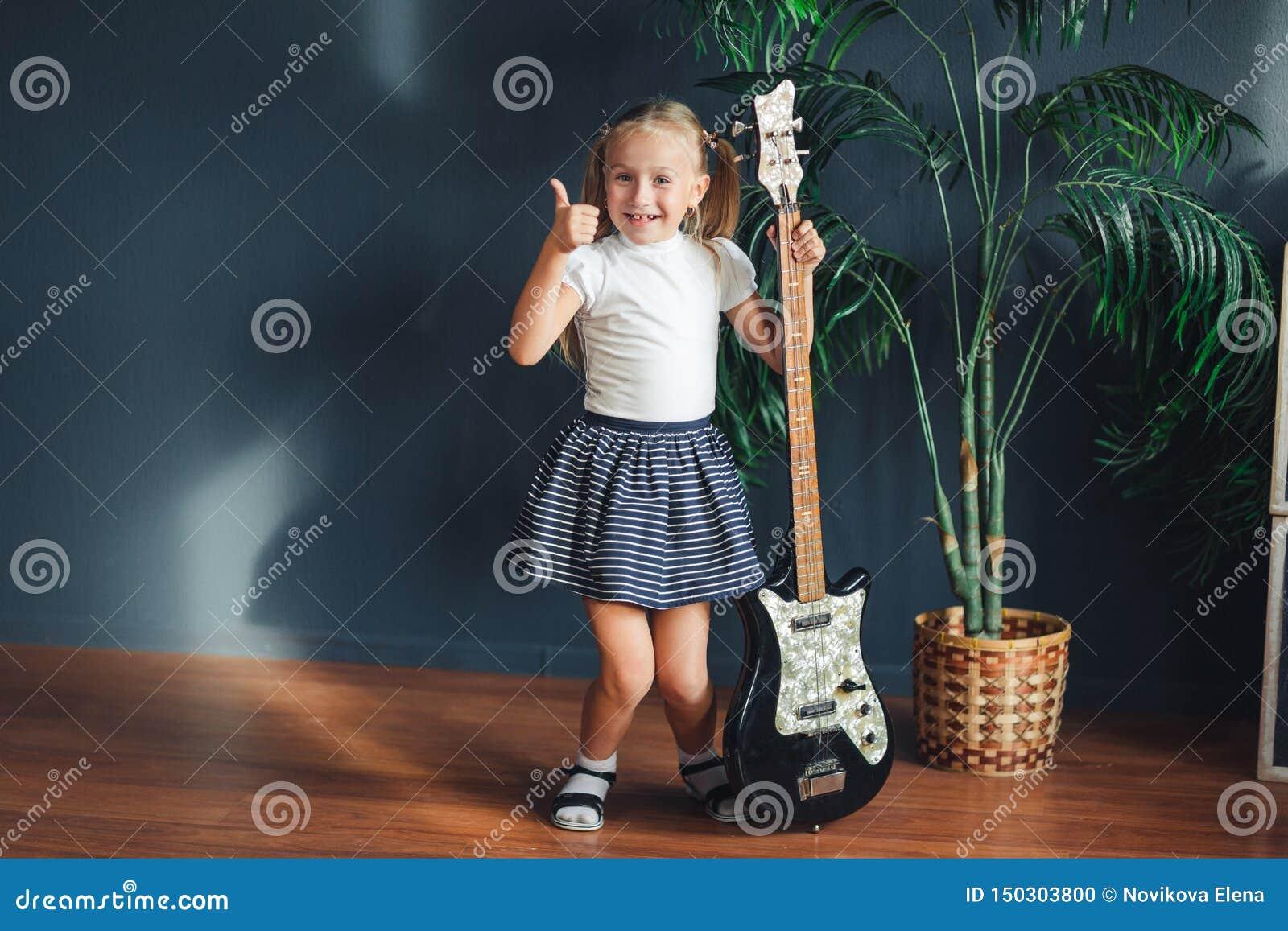 有尾巴的年轻白肤金发的女孩在白色T恤、裙子和凉鞋与电吉他在家显示看照相机的拇指和