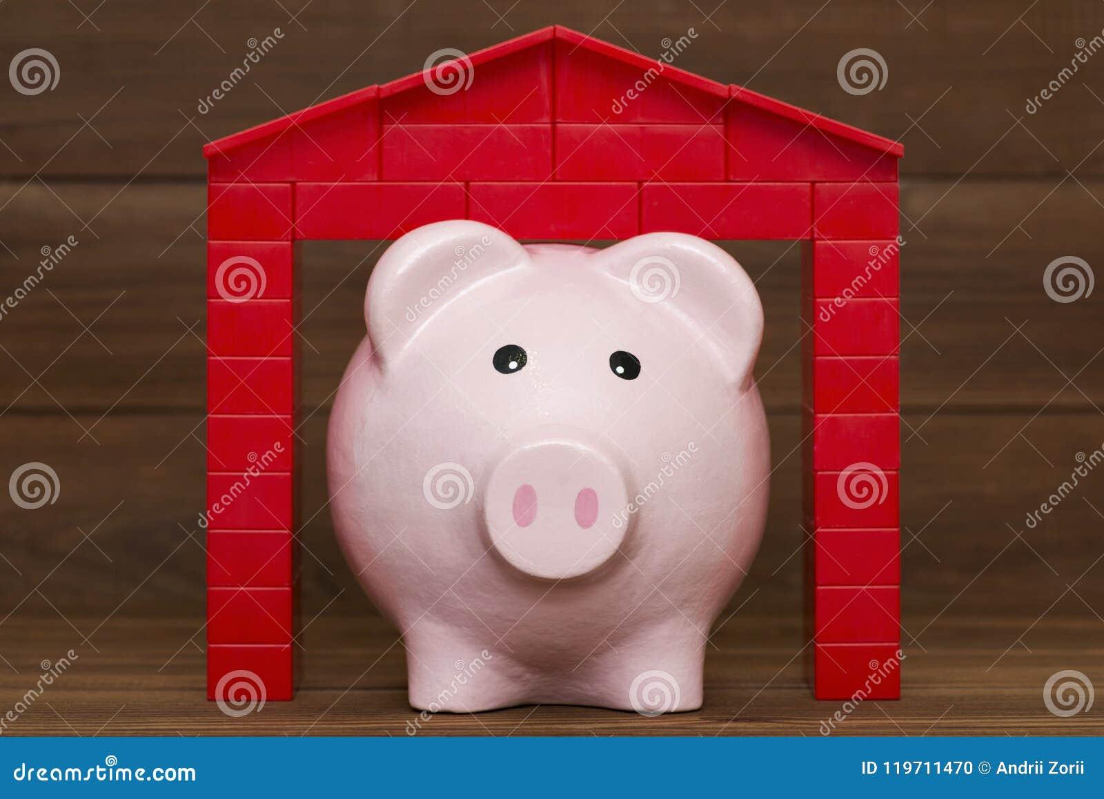 有屋顶的存钱罐在木背景