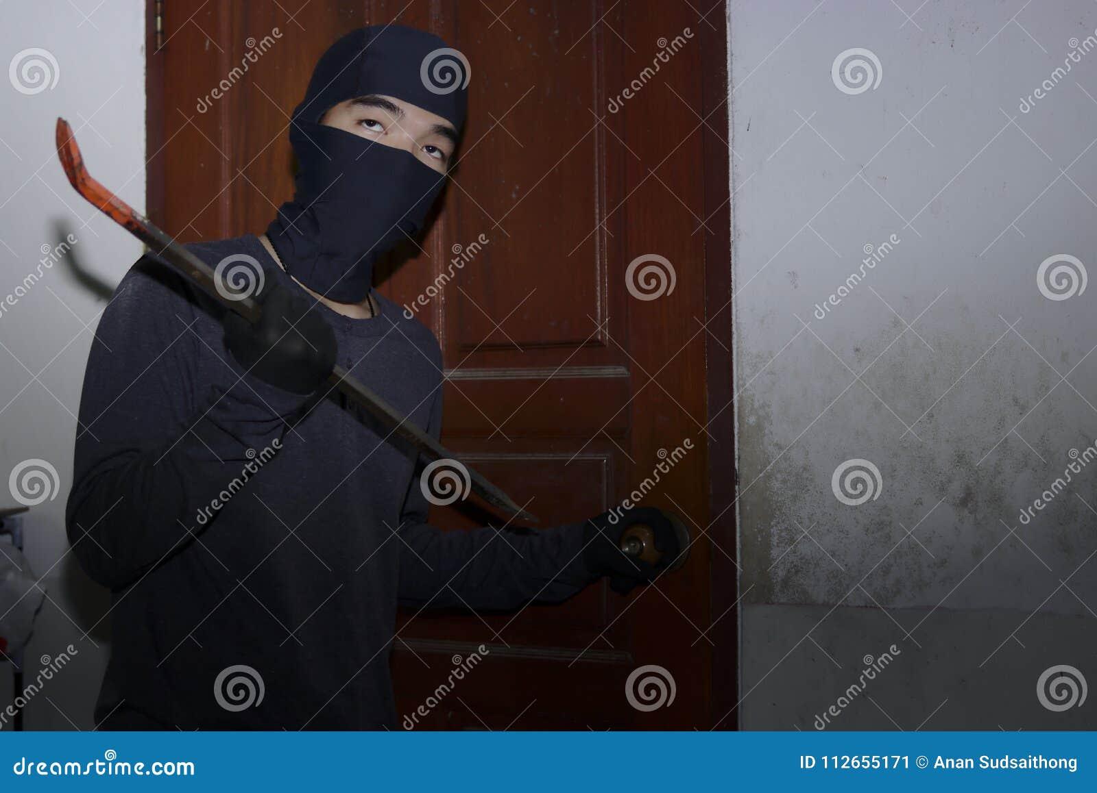 有巴拉克拉法帽的被掩没的窃贼使用对闯入的撬杠房子在夜间 砖概念罪行前面现有量苛刻的藏品手枪影子墙壁