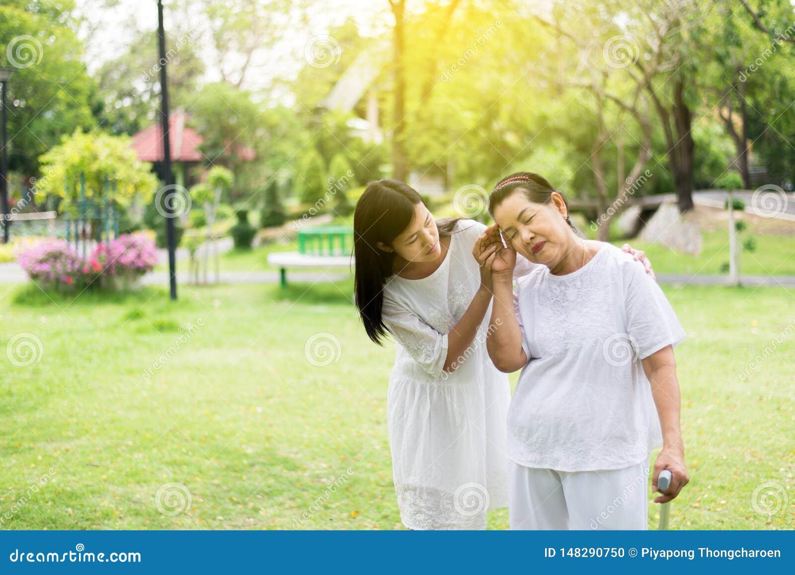 有年长亚裔的妇女从偏头痛疾病,女性的微弱的痛苦小心和支持