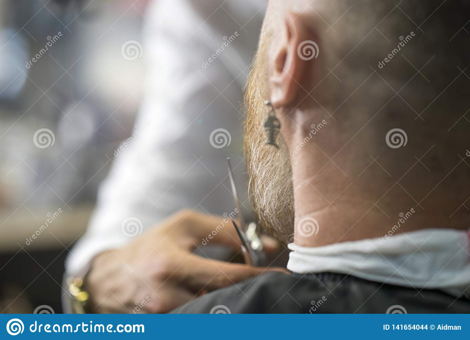 有异常的耳环的白种人人在理发店坐,当切开他的胡子时的专业理发师
