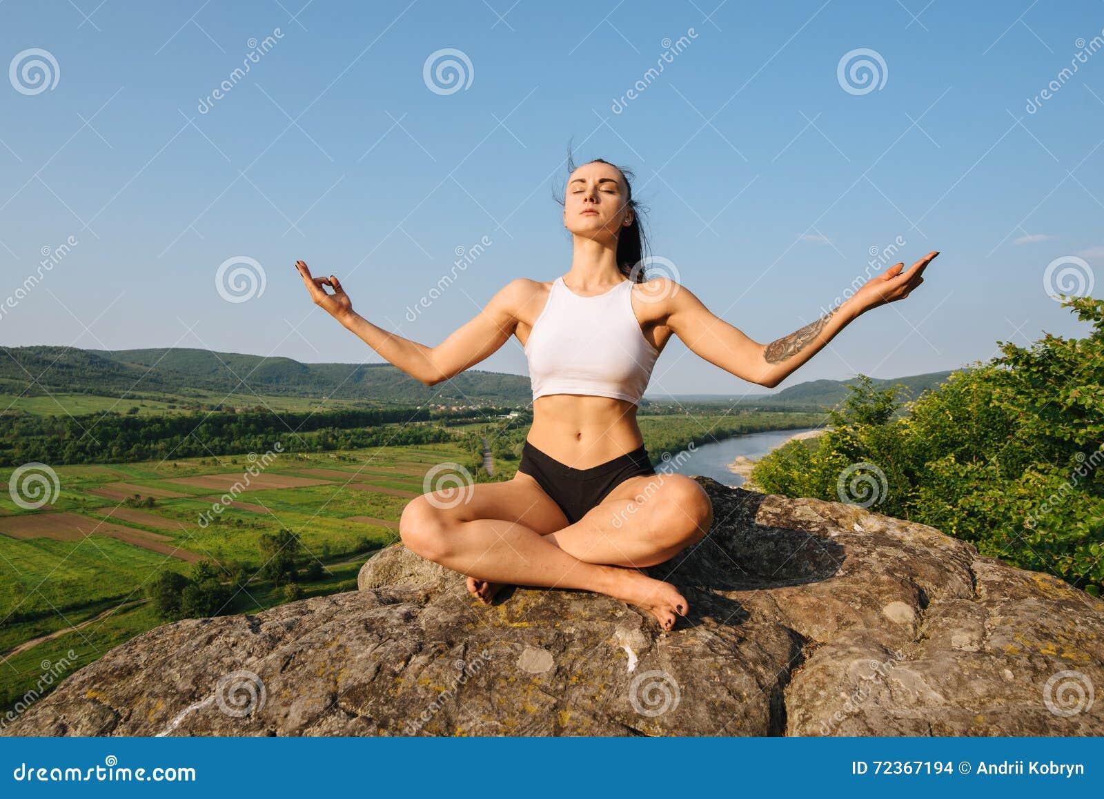 有强健的身体实践的瑜伽的深色的性感的运动妇女在反对蓝天的岩石 放松的片刻