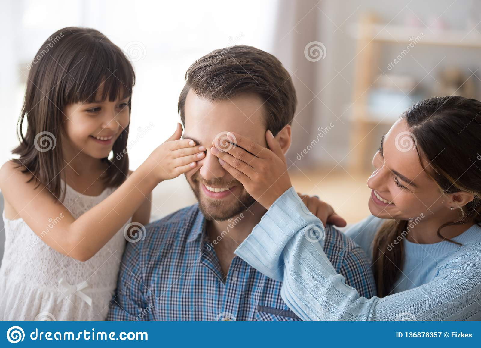 有微笑的爸爸的孩子关闭的眼睛的妻子做惊奇