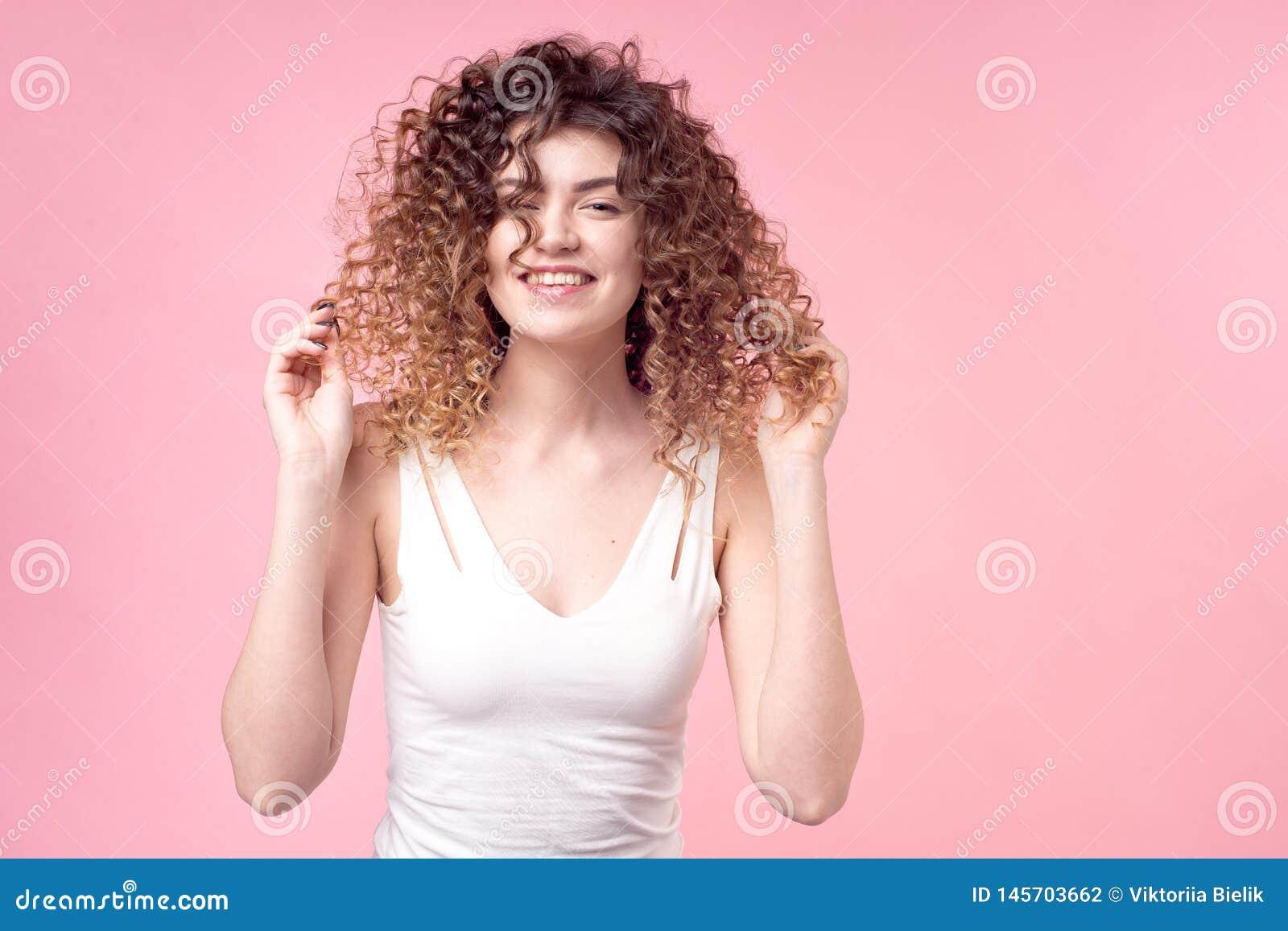 有微笑的美女在与令人惊讶的卷毛的面孔在白色T恤deloet放置手拿着辅助部件