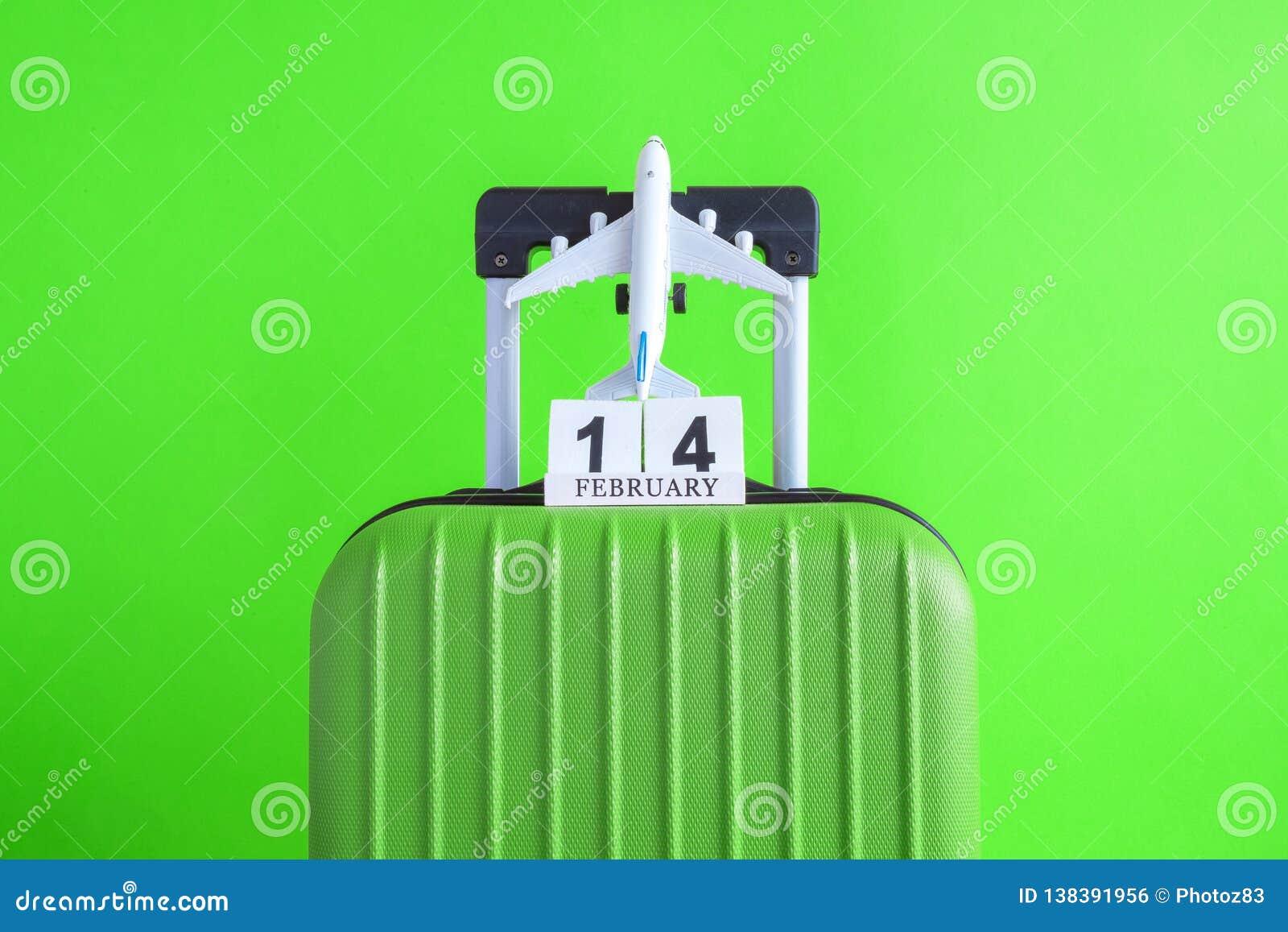 有情人节日期日历的在绿色背景minimalistic假期概念的行李和飞机
