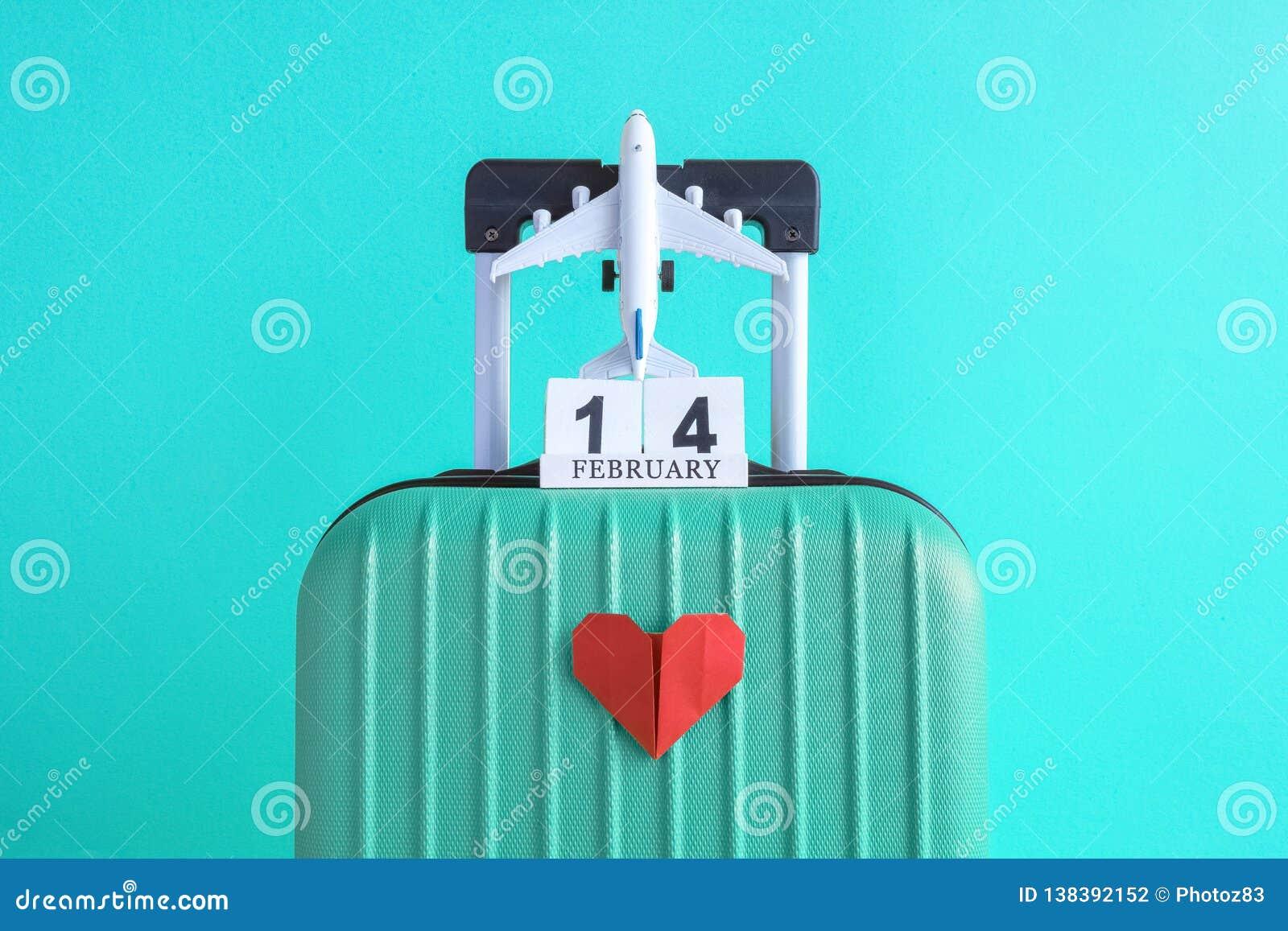 有情人节日期日历的有纸心脏的行李和飞机在绿松石背景minimalistic假期概念