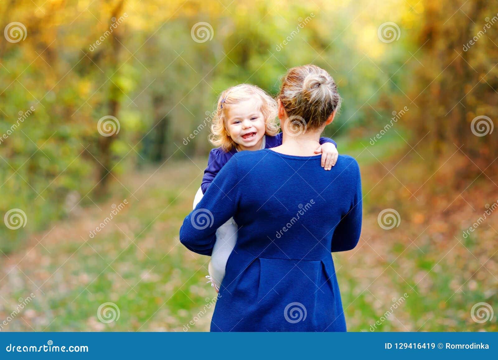 有愉快的年轻的母亲乐趣逗人喜爱的小孩女儿,家庭画象一起 有美丽的女婴的妇女本质上