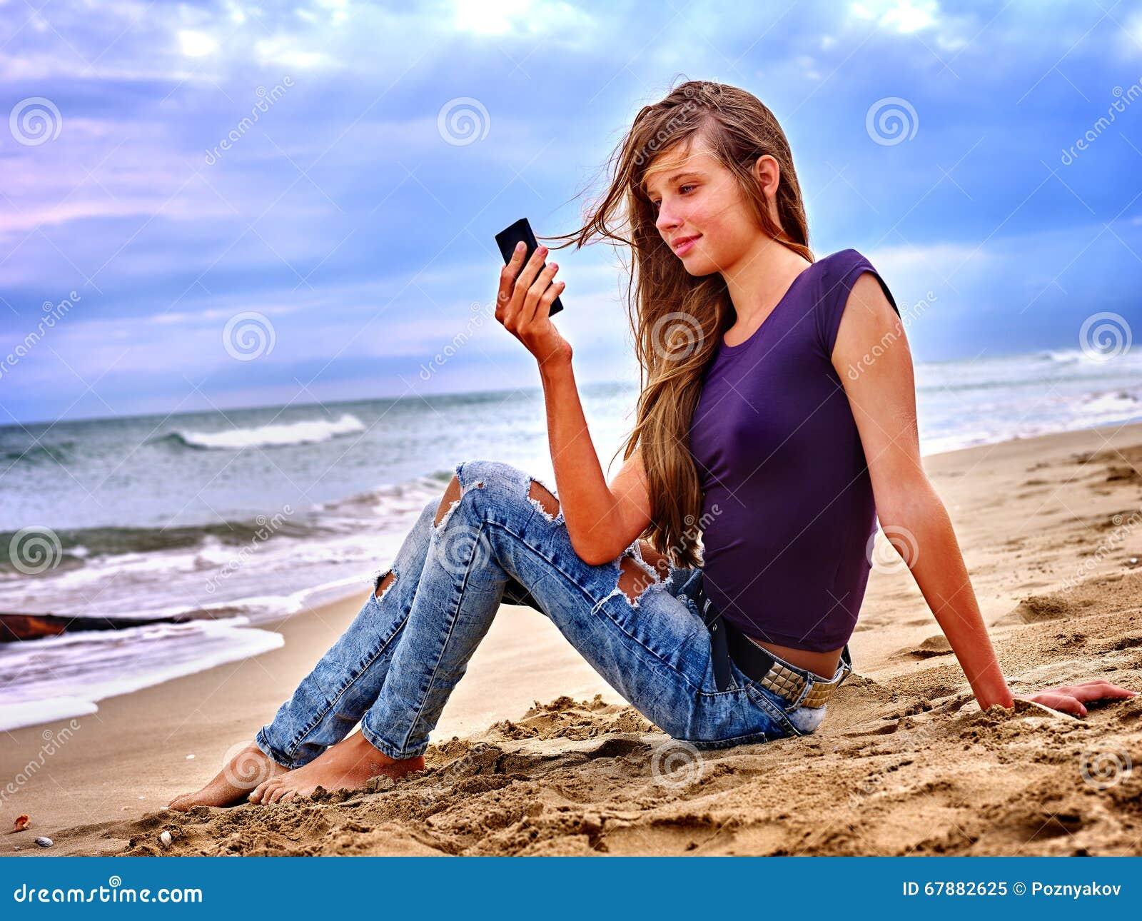 有手机的女孩坐沙子在海附近