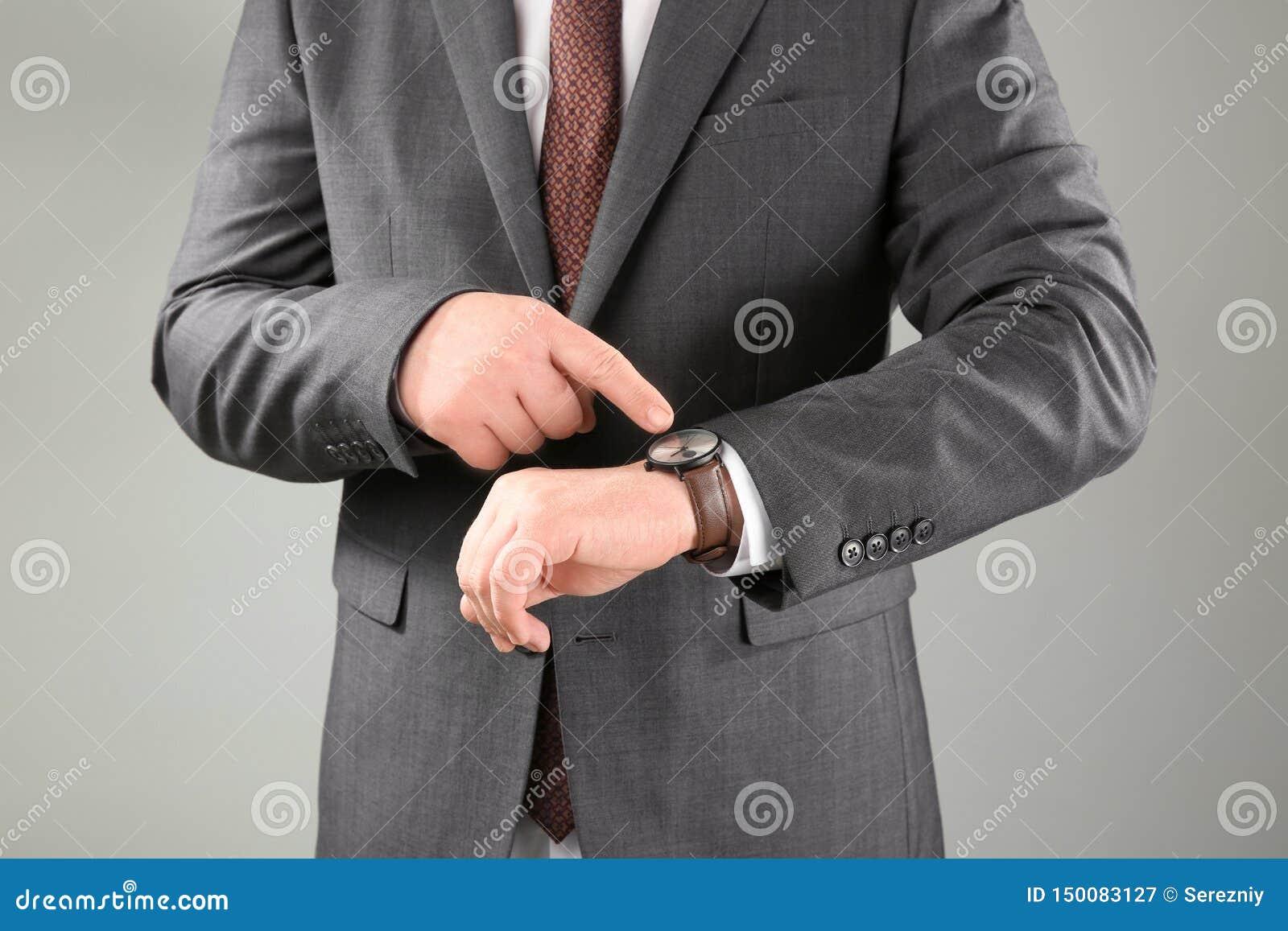 有手表的人反对灰色背景 E