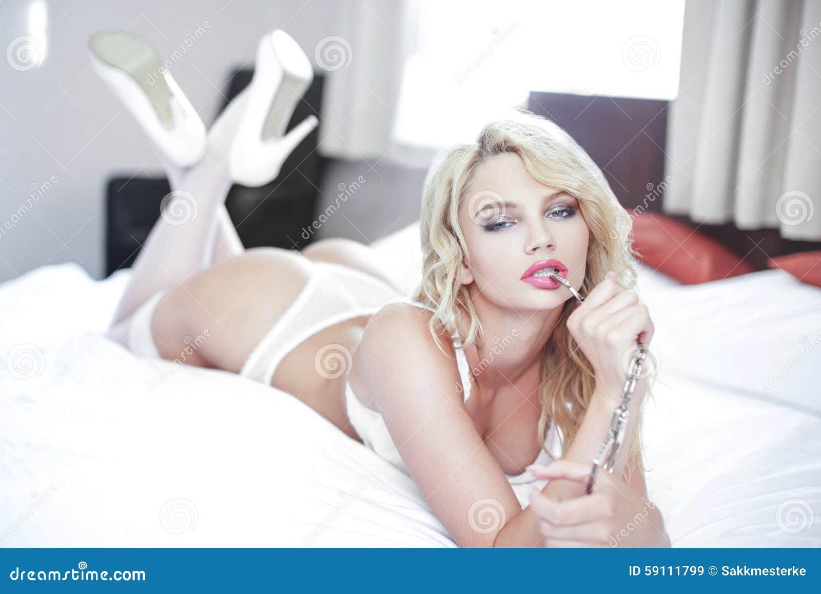 有手铐的性感的白肤金发的妇女在床上
