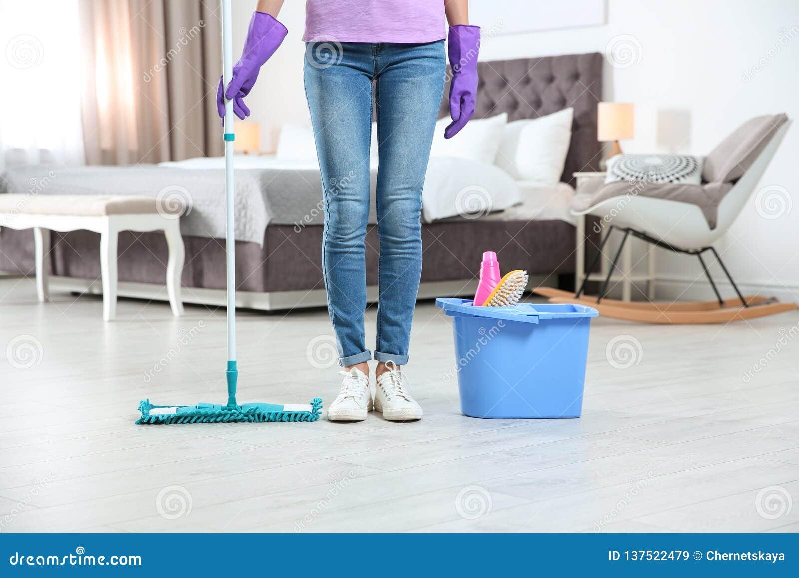 有拖把的年轻女人和洗涤剂在卧室 清洁服务