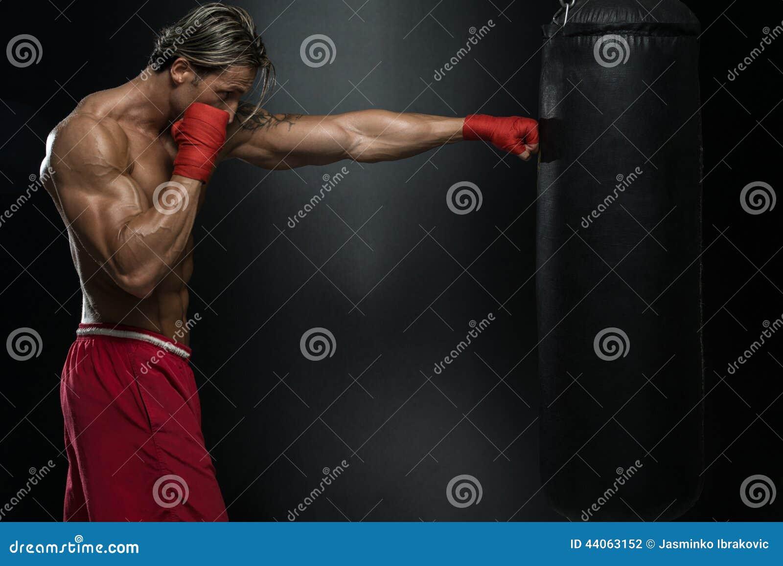有纹身花刺的在红色拳击手套-在黑背景的拳击一个人-一种健康生活