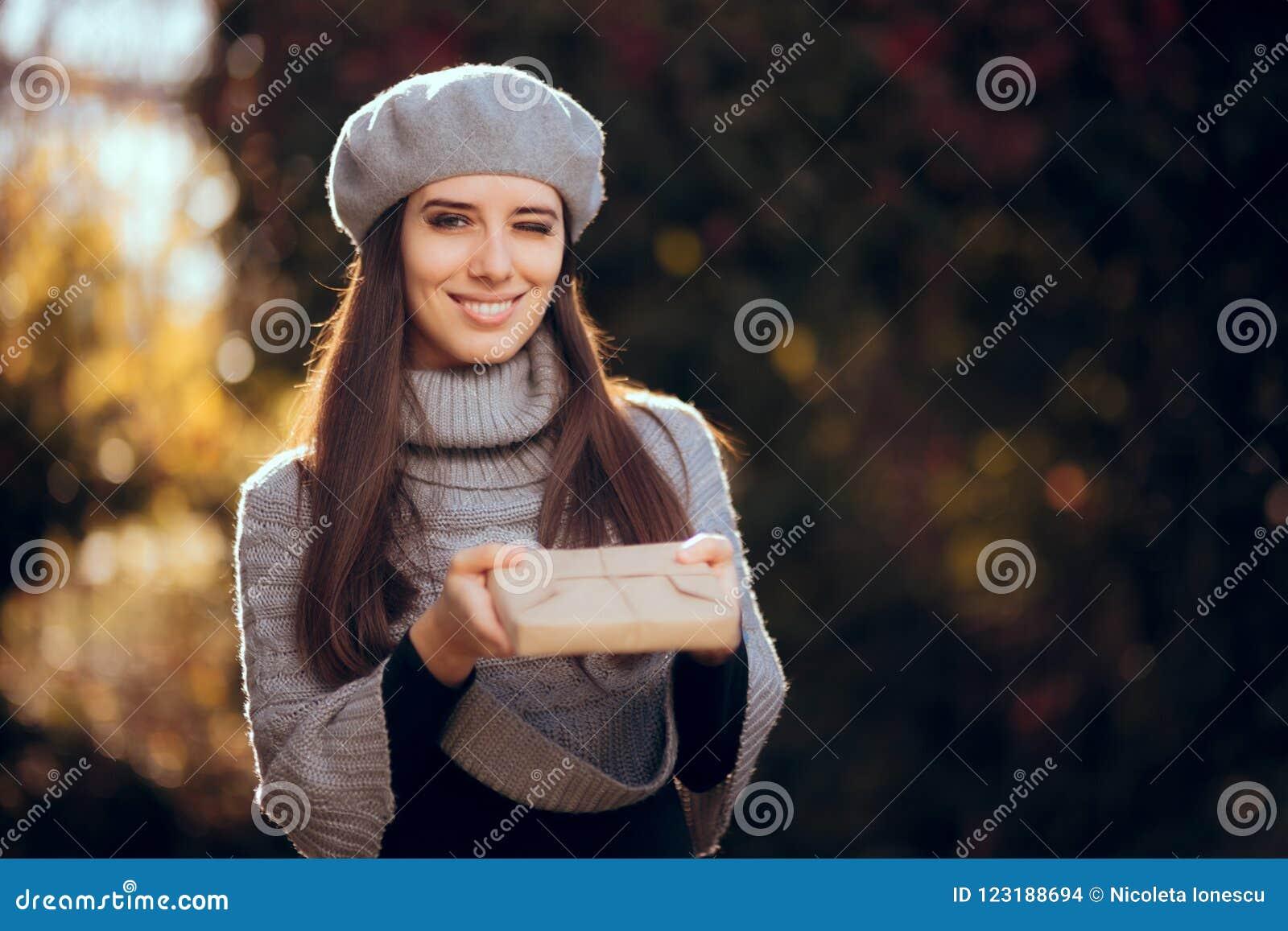 有拿着一个包装纸包裹的贝雷帽的减速火箭的别致的女孩