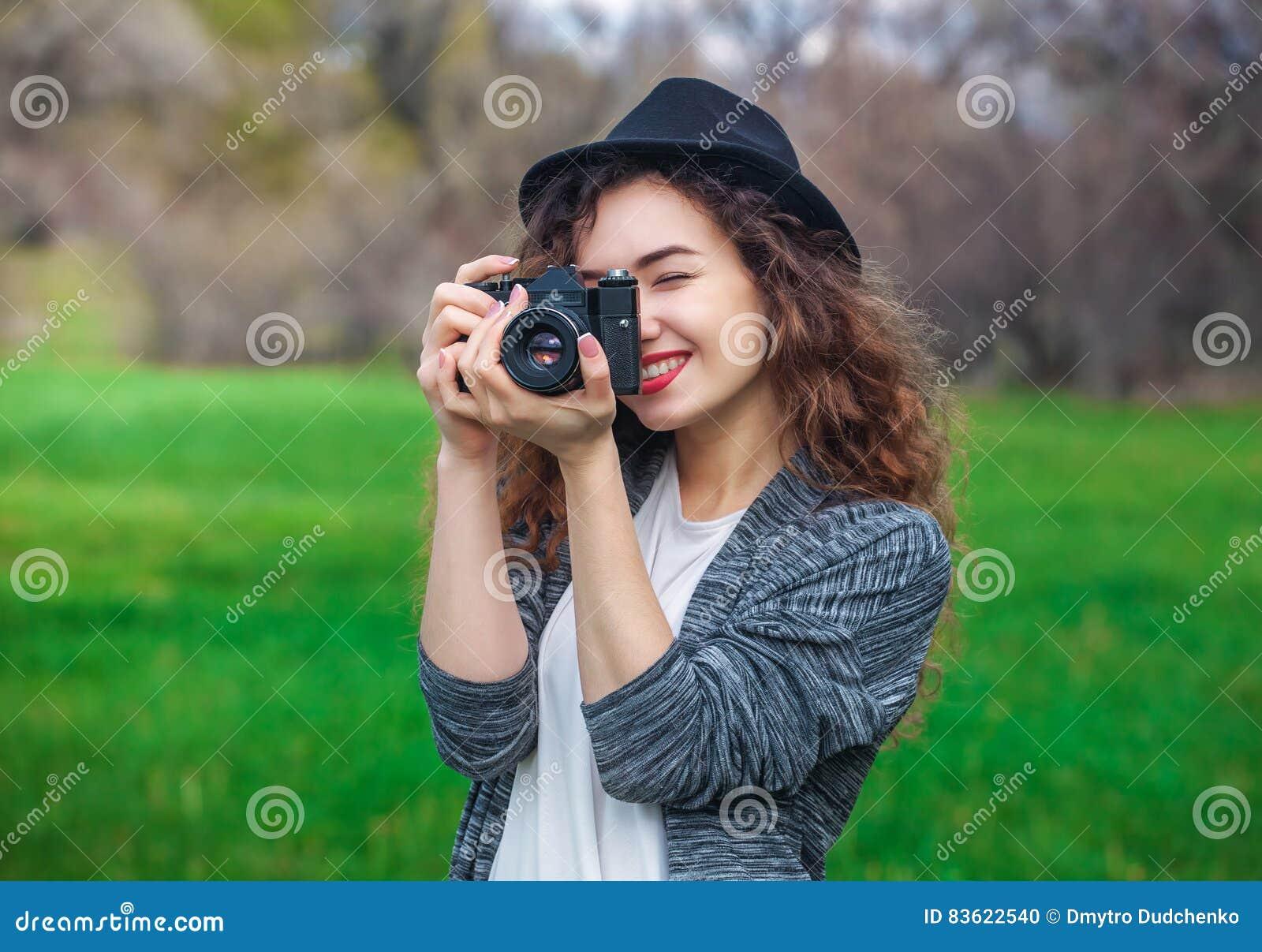 有拿着一台老照相机的卷发的美丽的女孩摄影师和拍照片
