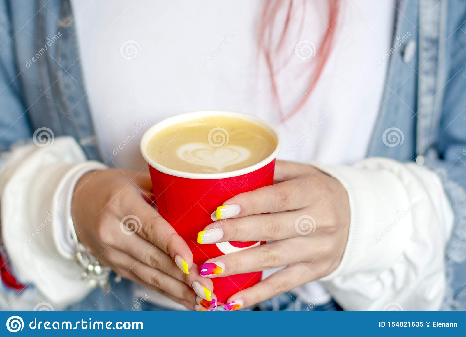 有拿着一杯红色咖啡与被绘的心脏的明亮的夏天修指甲的手女孩