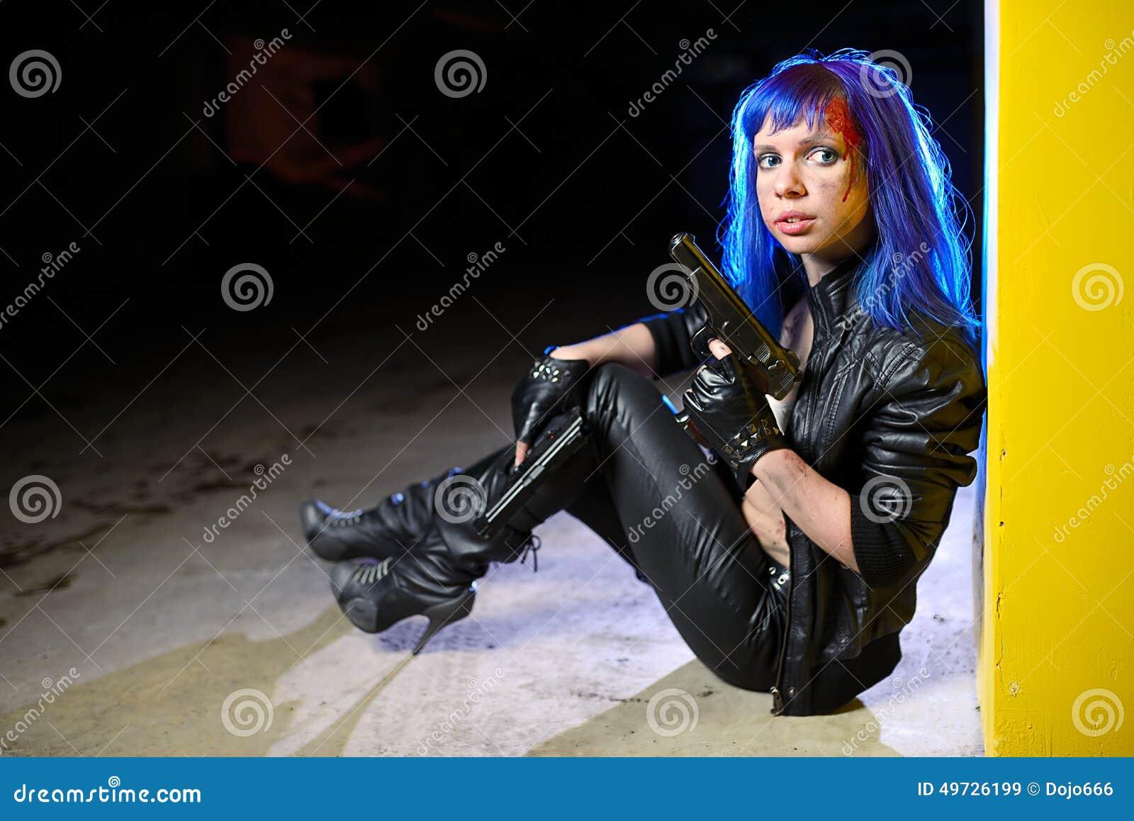 有拿着两杆枪和看作为凶手的蓝色头发的性感的妇女