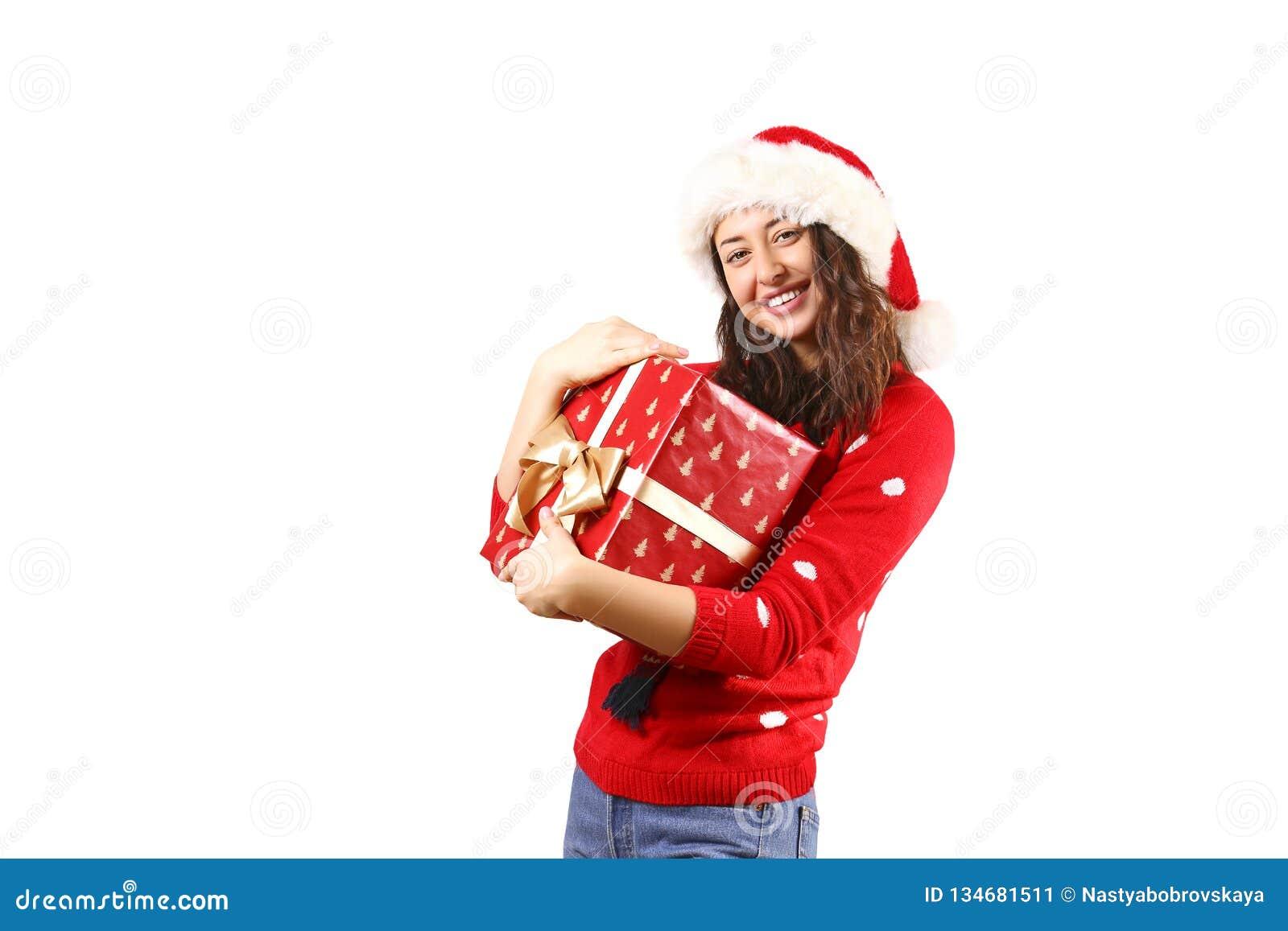 有拿着礼物的长的卷发佩带的圣诞老人项目帽子andd的年轻深色的妇女