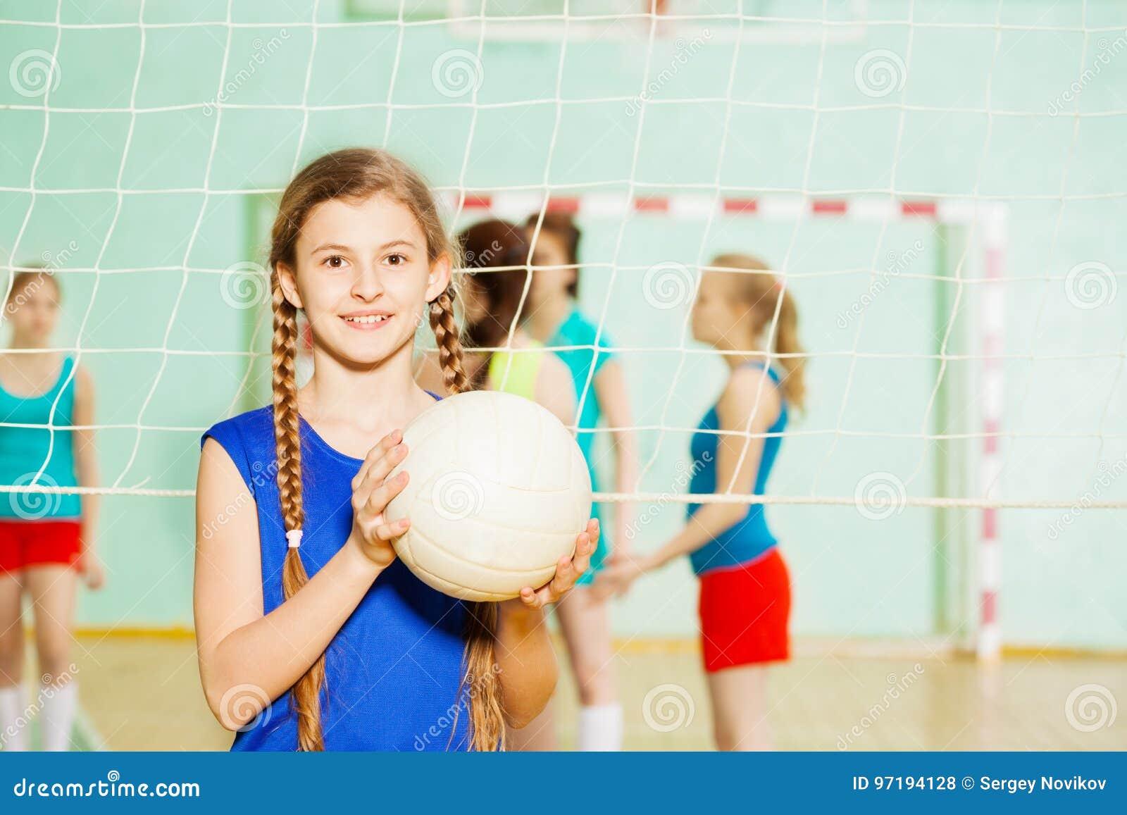 有排球球的青少年的女孩在体育馆里