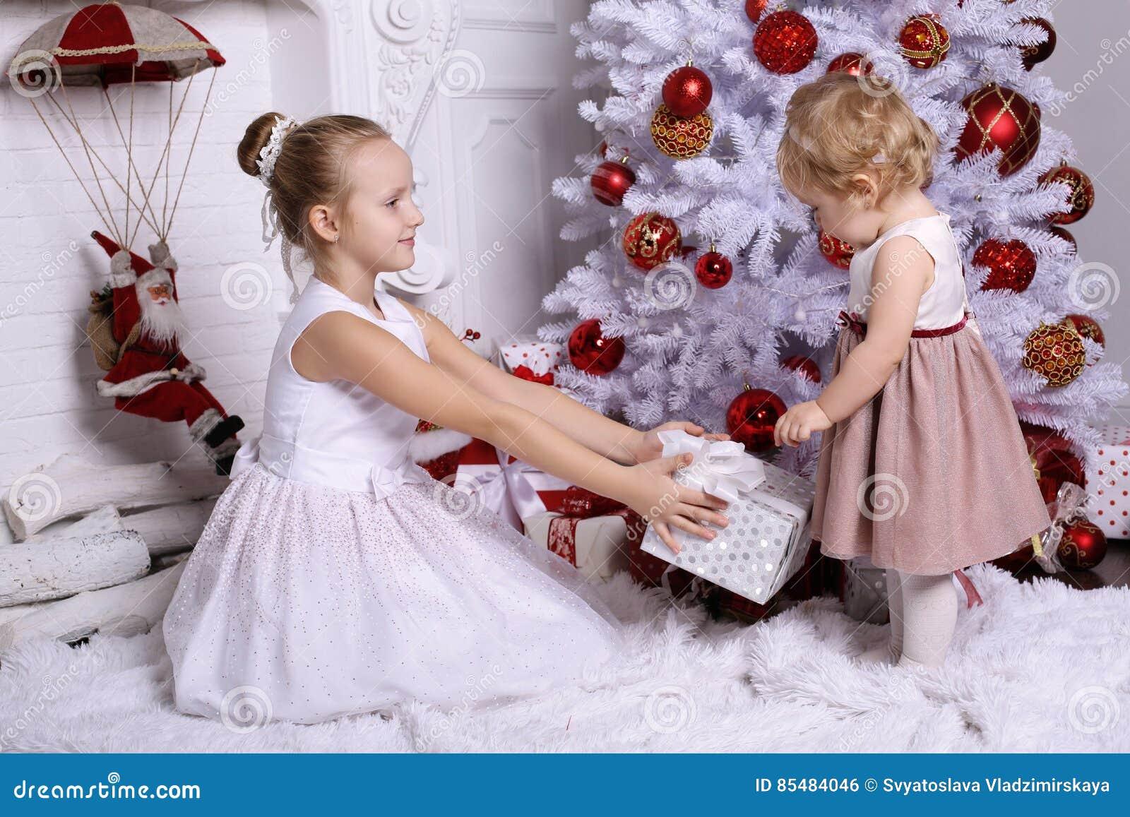 有摆在圣诞树旁边的金发的可爱的姐妹