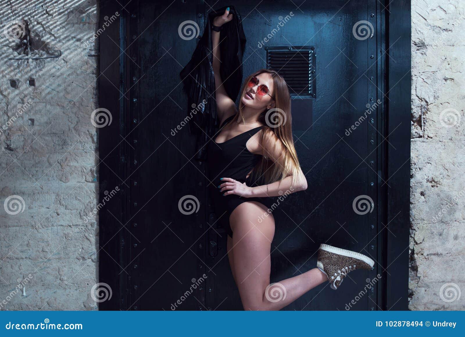有摆在泳装和太阳镜的完善的适合身体的热的少妇拿着夹克反对黑背景