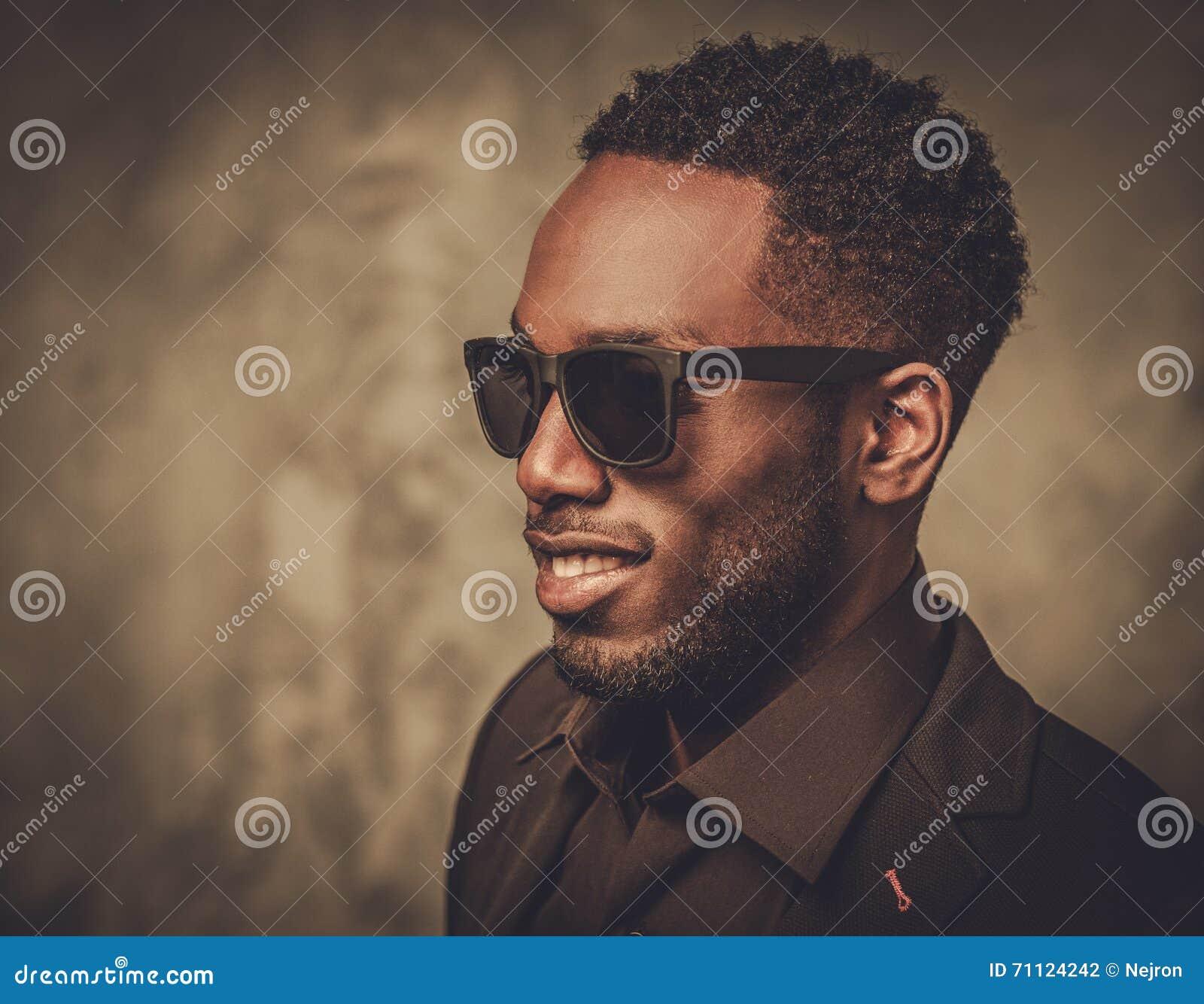 有摆在黑暗的背景的太阳镜的微笑的黑人