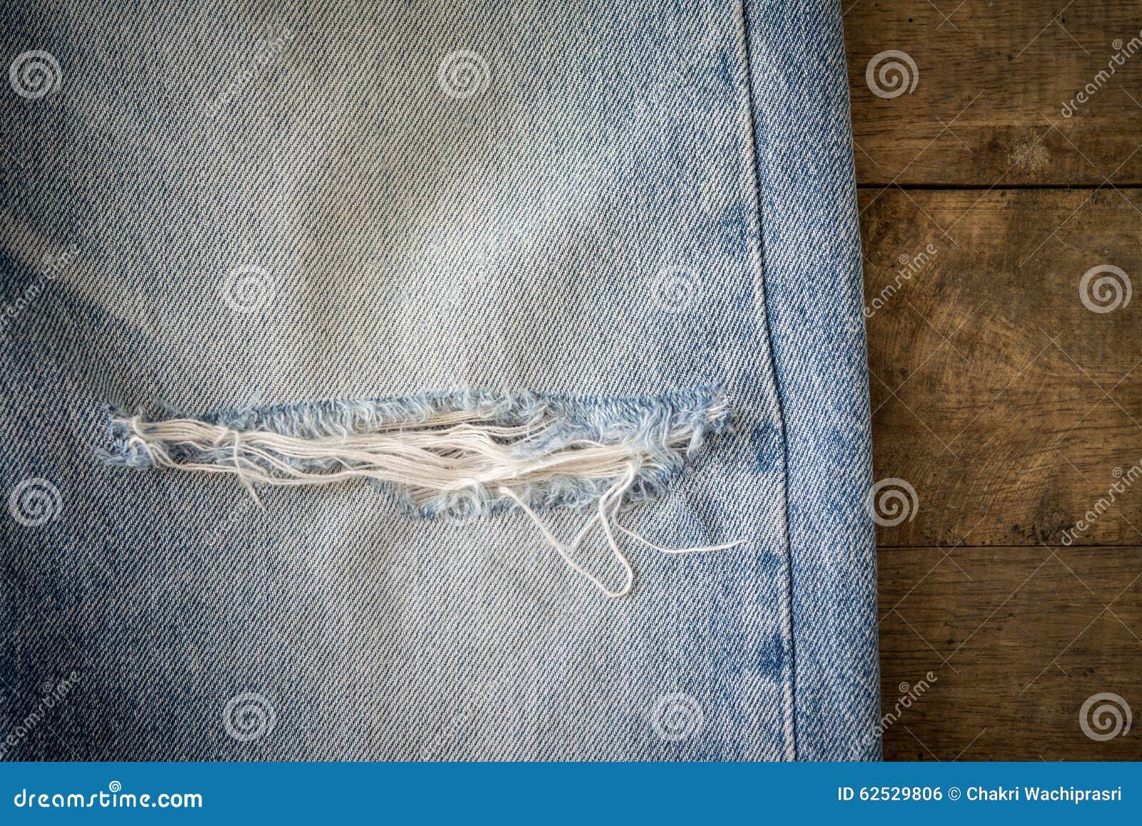 有撕毁的老蓝色牛仔裤在木背景