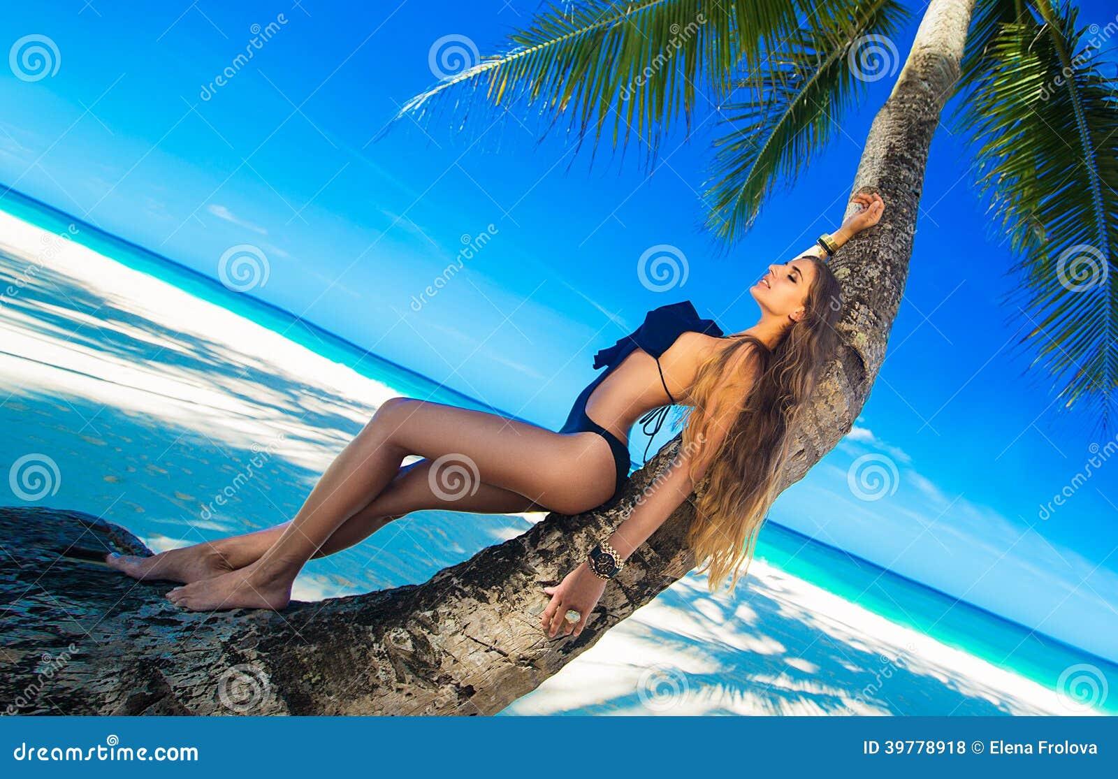 有放松在棕榈海的长的头发的美丽的少妇