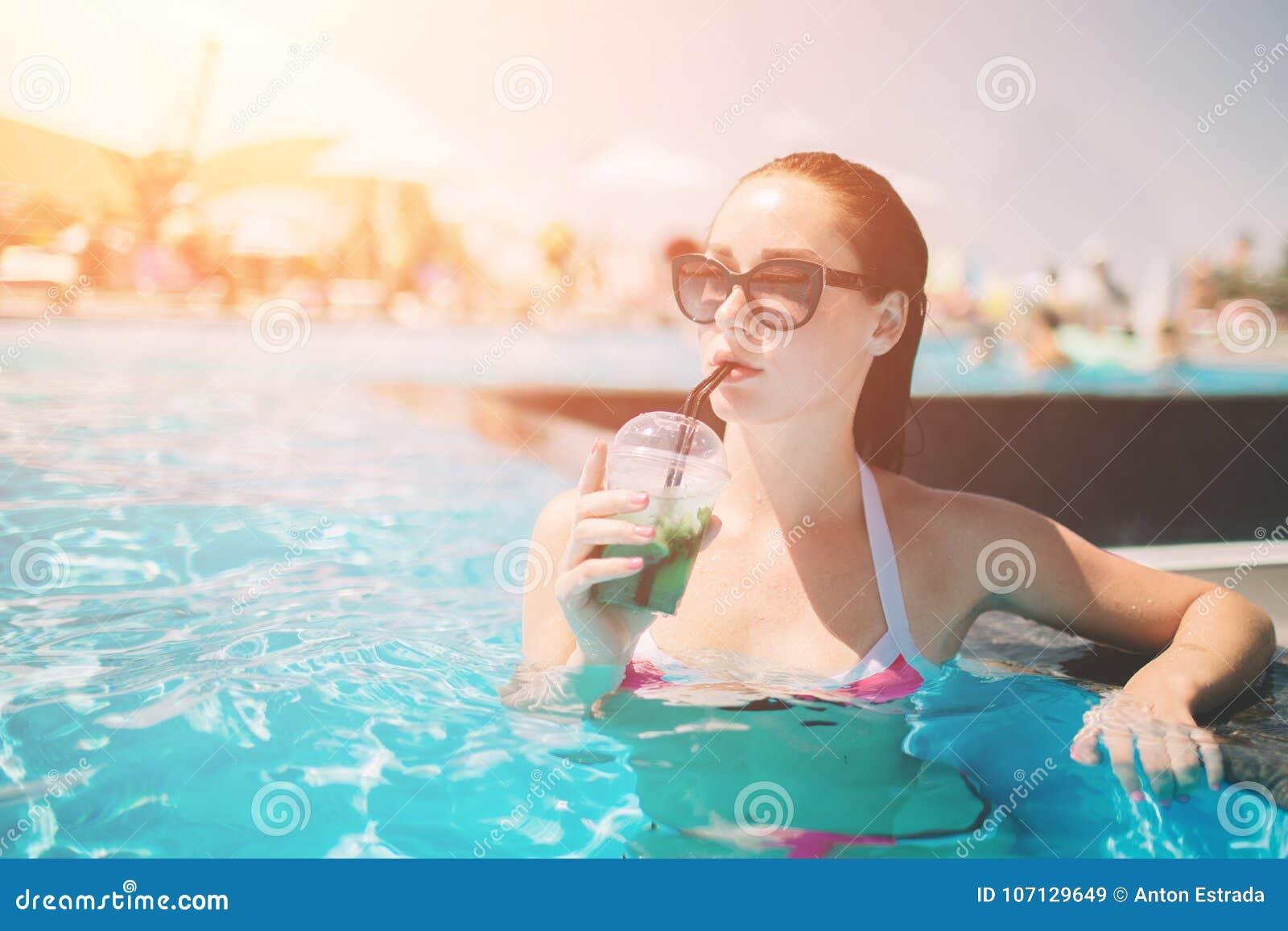 有放松在游泳池的鸡尾酒的深色的女孩 比基尼泳装的性感的妇女享用夏天太阳和晒黑在期间的