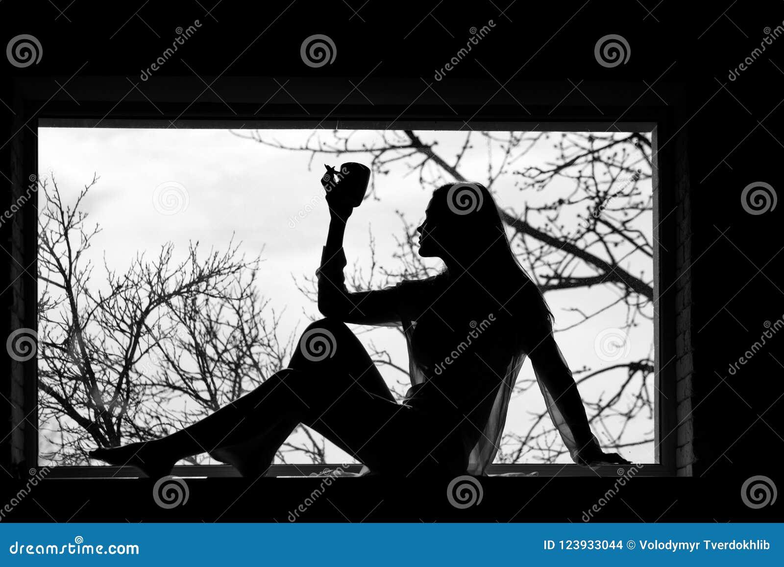 有放置在窗口的礼服的妇女