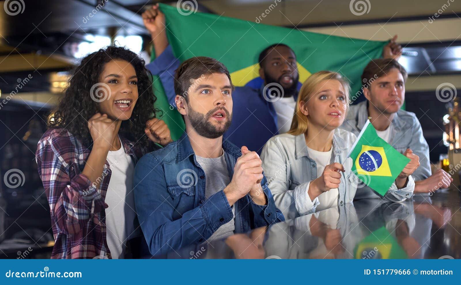 有旗子的巴西足球迷欢呼为国家队的,盼望胜利
