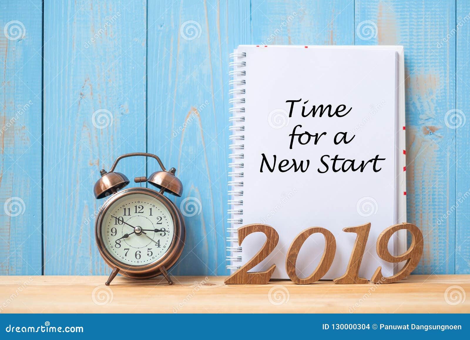 有时刻的2019新年快乐的在笔记本、减速火箭的闹钟和木数字的新的起动文本在桌和拷贝空间上