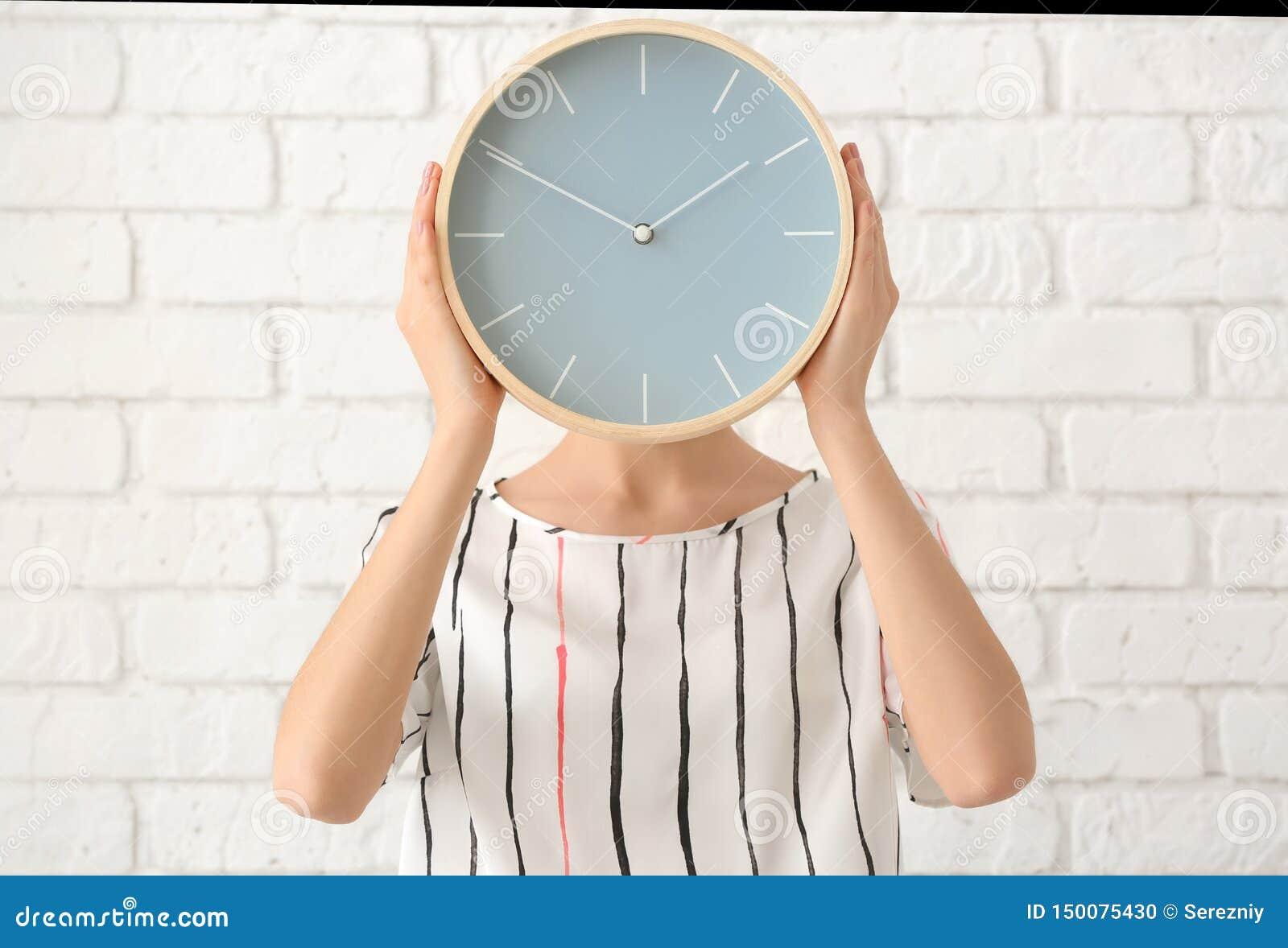 有时钟的妇女在砖墙背景 E