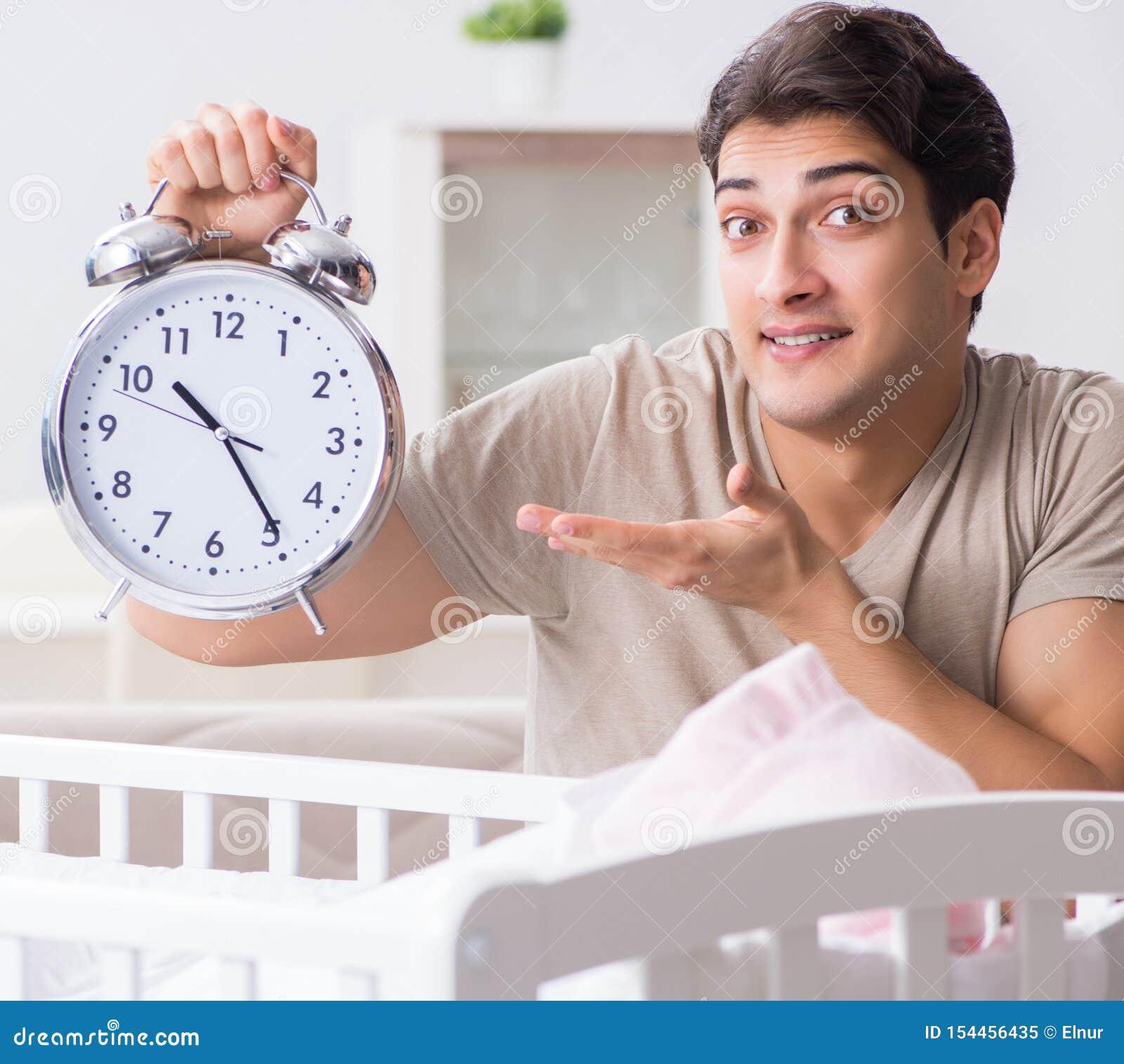有时钟的年轻爸爸在新生儿婴孩床轻便小床附近