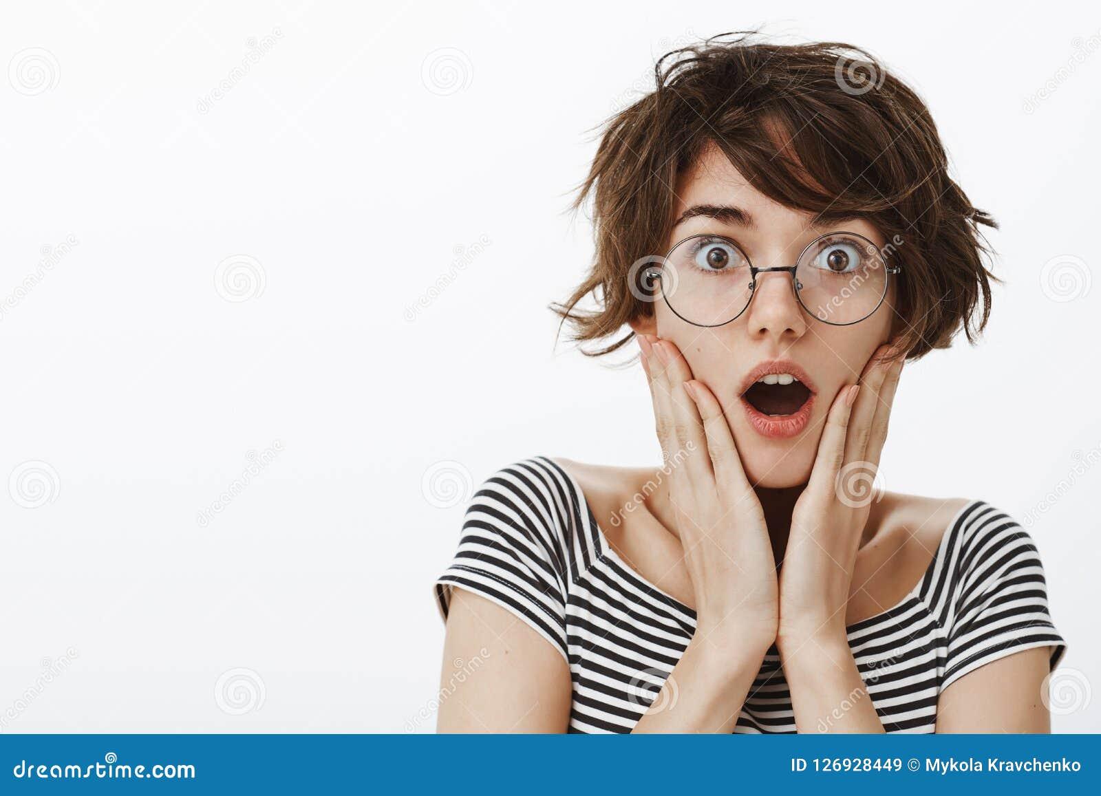 有时髦的短的理发的被打动的和震惊迷人的女性在圆的时髦玻璃,喘气的和落下的下颌