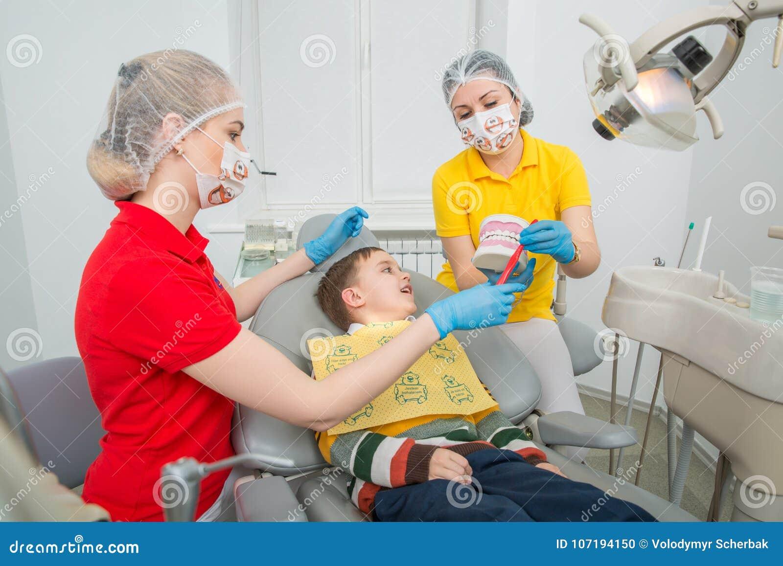 有显示小男孩如何的助理的牙医清洗牙与在一个人为下颌钝汉的一把牙刷