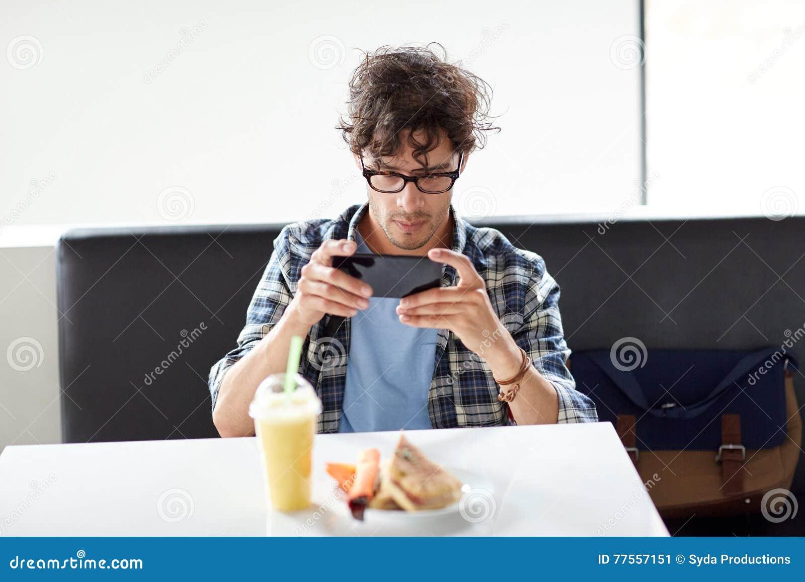 有智能手机的人拍摄食物的在咖啡馆