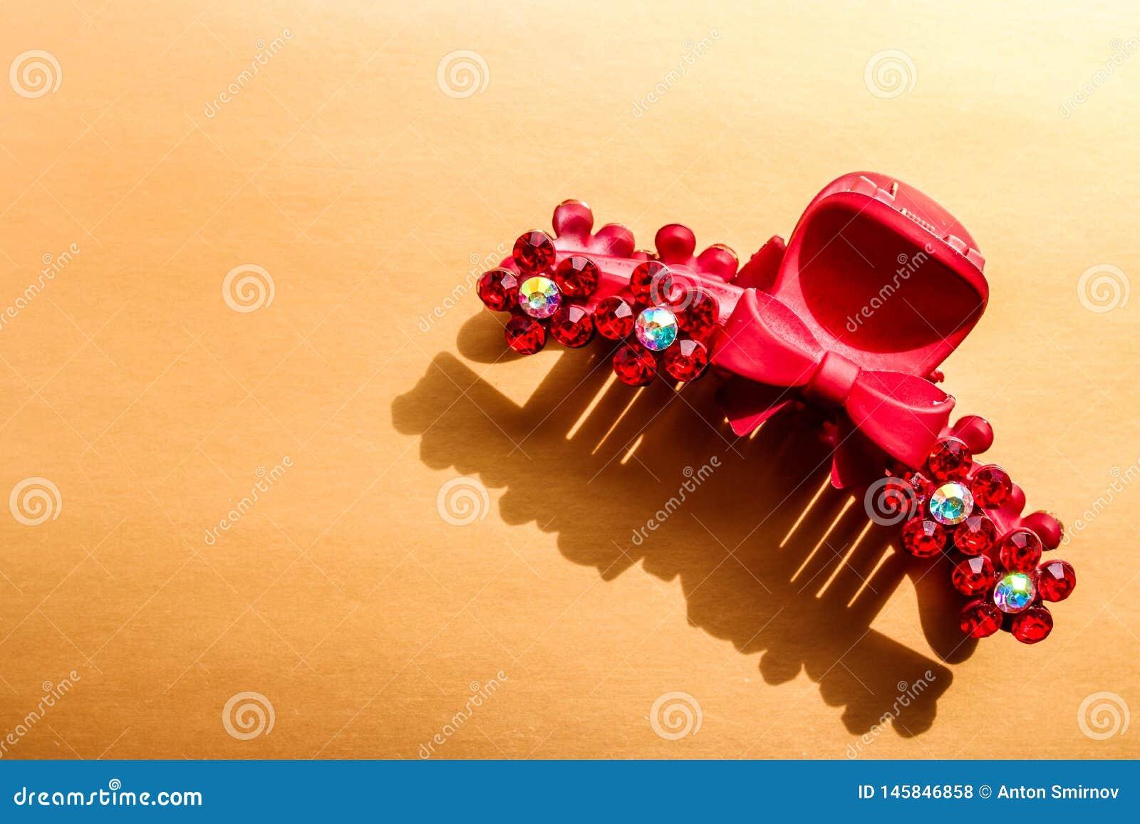 有有假钻石的塑料红色发夹在古铜色背景
