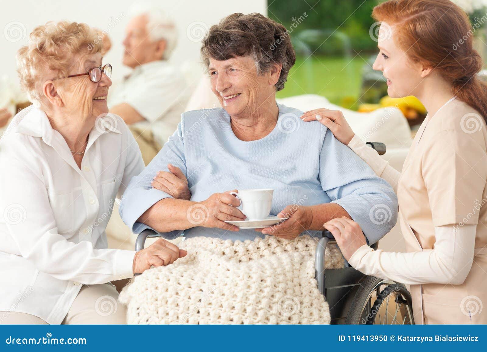 有朋友和护士的微笑的被麻痹的资深妇女
