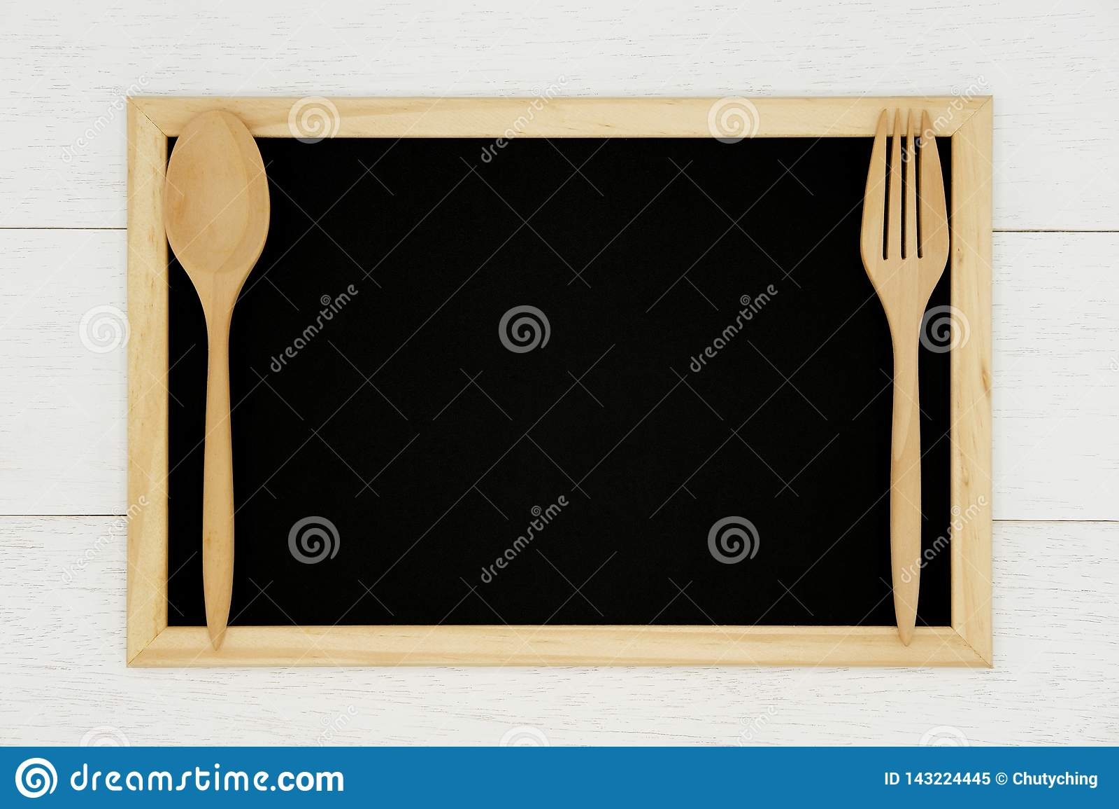 有木匙子的空白的在白色木板条背景的黑板和叉子