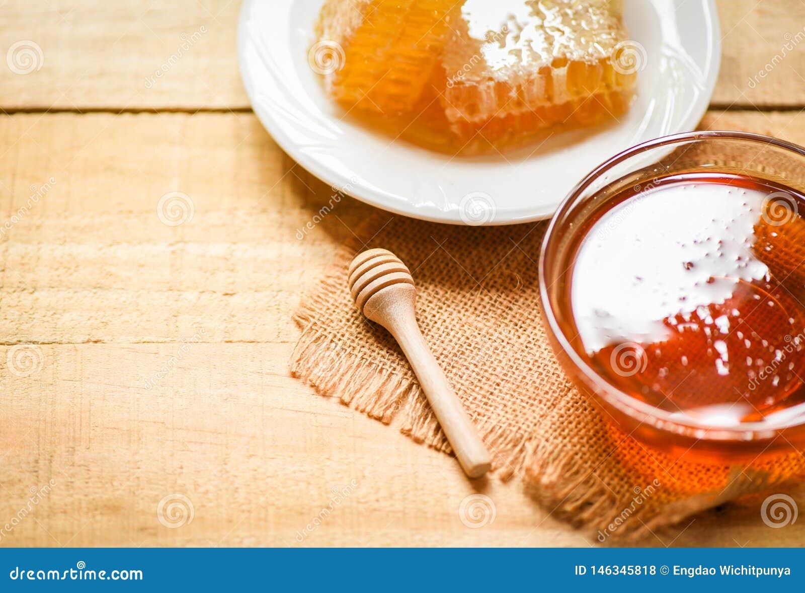 有木浸染工的新鲜的甜蜂蜜在白色板材的瓶子和蜂窝在木桌背景