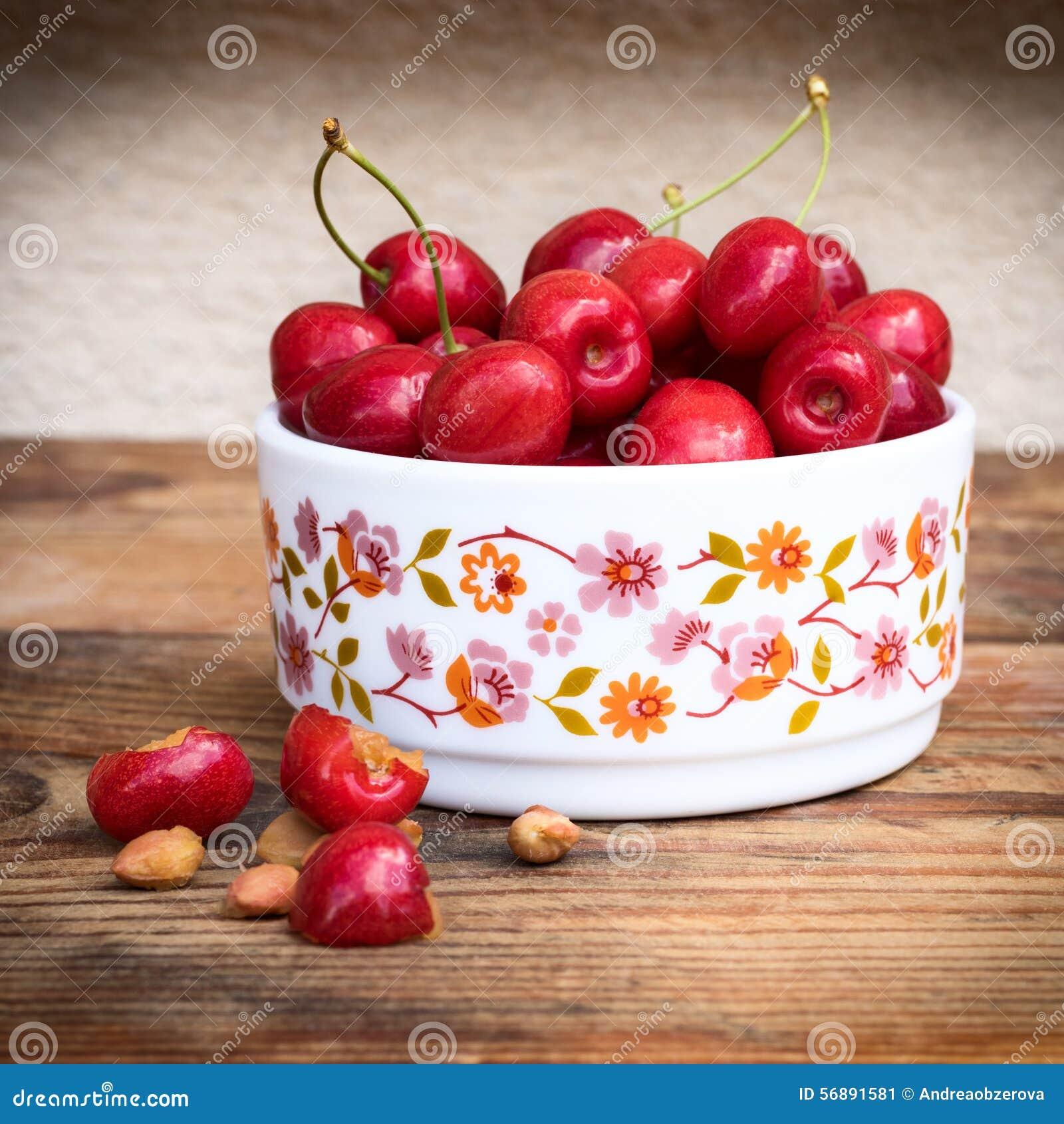有机本地出产的樱桃和石头在葡萄酒陶瓷碗,在木背景