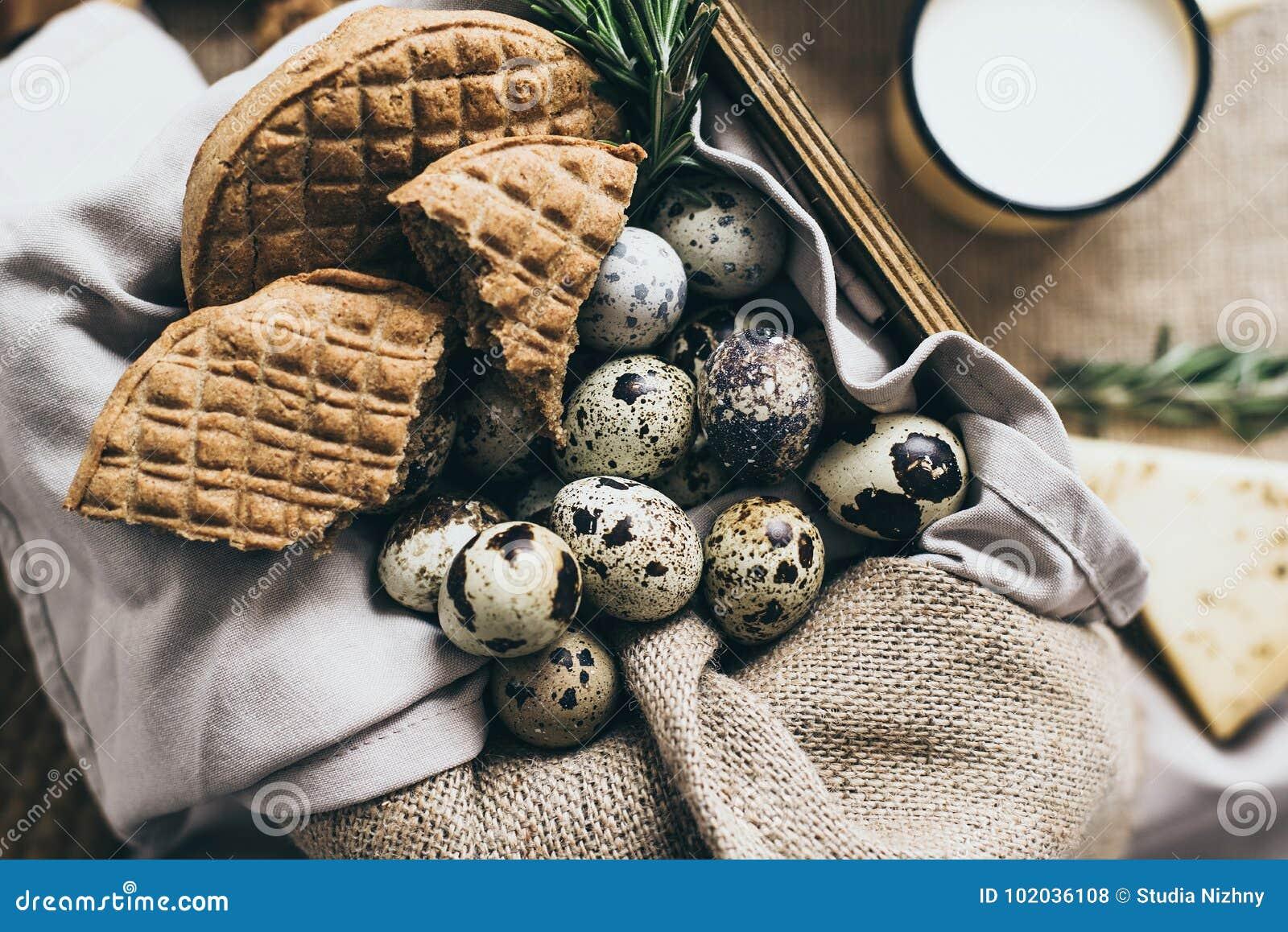 有机食品的时髦的构成为早餐鸡蛋,乳酪做准备 面包和草本在一个盘,在木切口