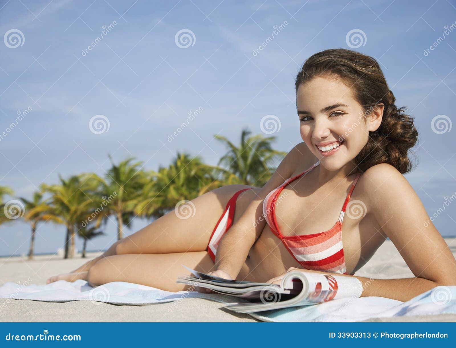有杂志的微笑的十几岁的女孩在海滩