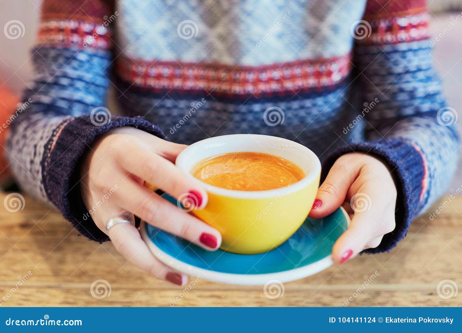 有杯子的妇女手热的咖啡