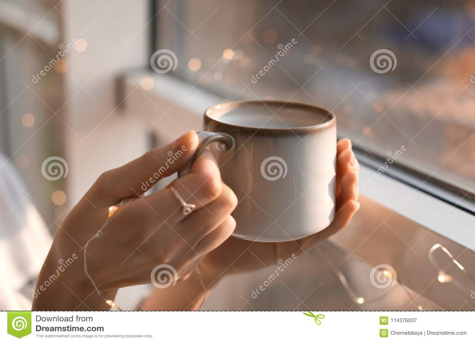 有杯子的少妇在窗口附近的热的咖啡