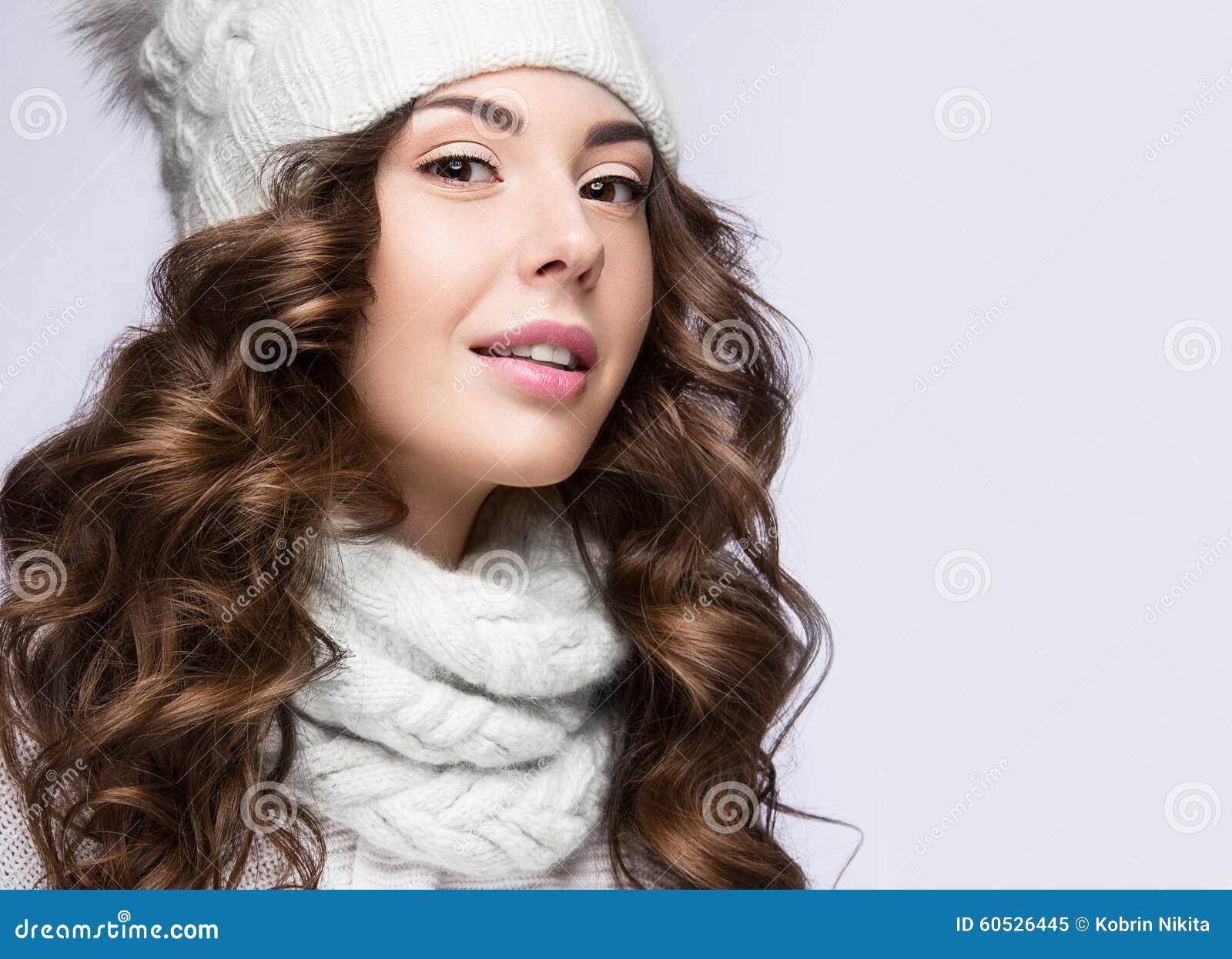 有柔和的构成、卷毛和微笑的美丽的女孩在白色编织帽子 温暖的冬天图象 秀丽表面
